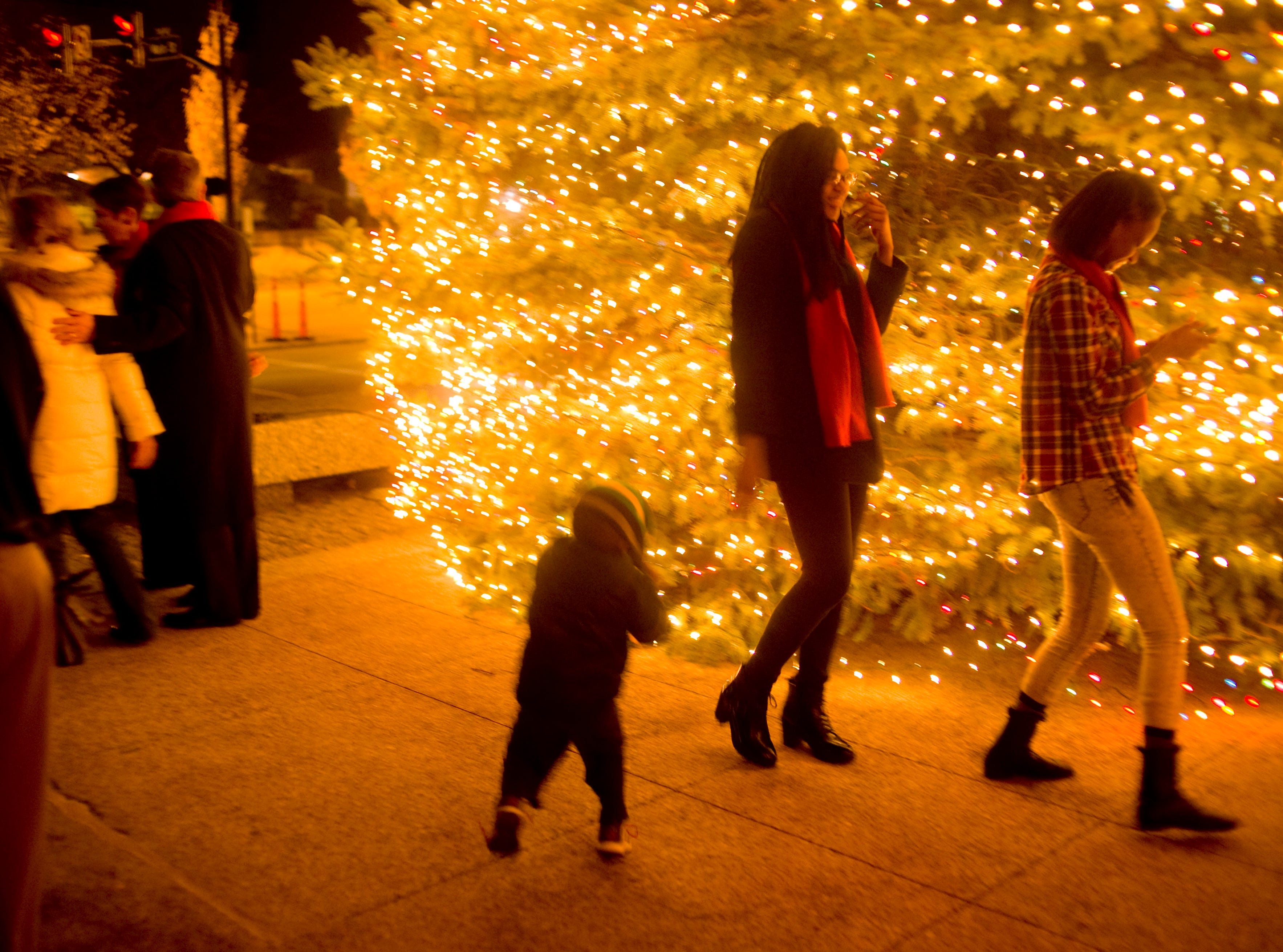 Ethan Wagner, 3, (left) Ahlaysha Riley, 15, (center) and Unique Stanfield, 16, gather around the City of Evansville's Christmas tree for family pictures Friday night.
