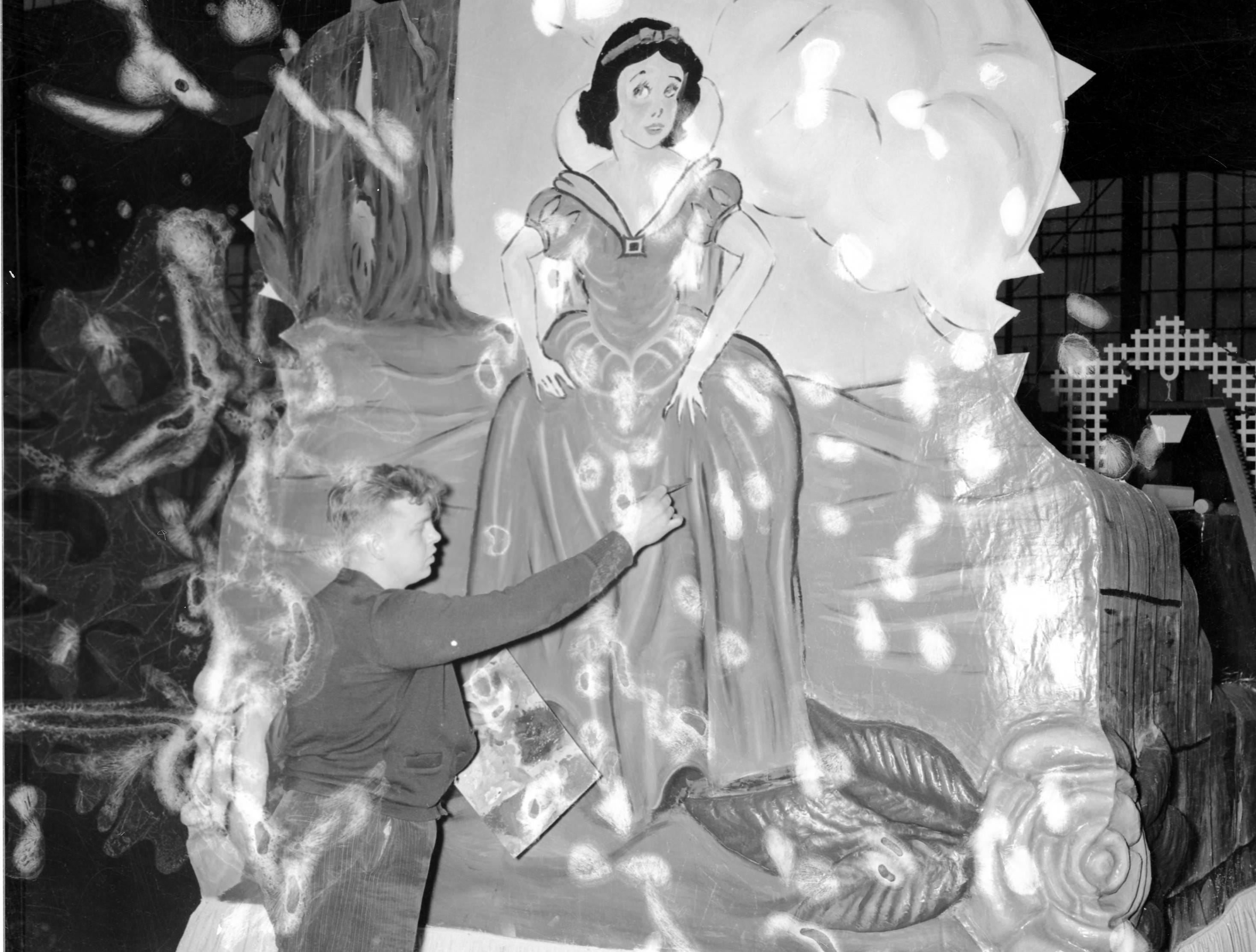 Man putting the final touches on float with Snow White for the WPA Christmas parade in 1939
