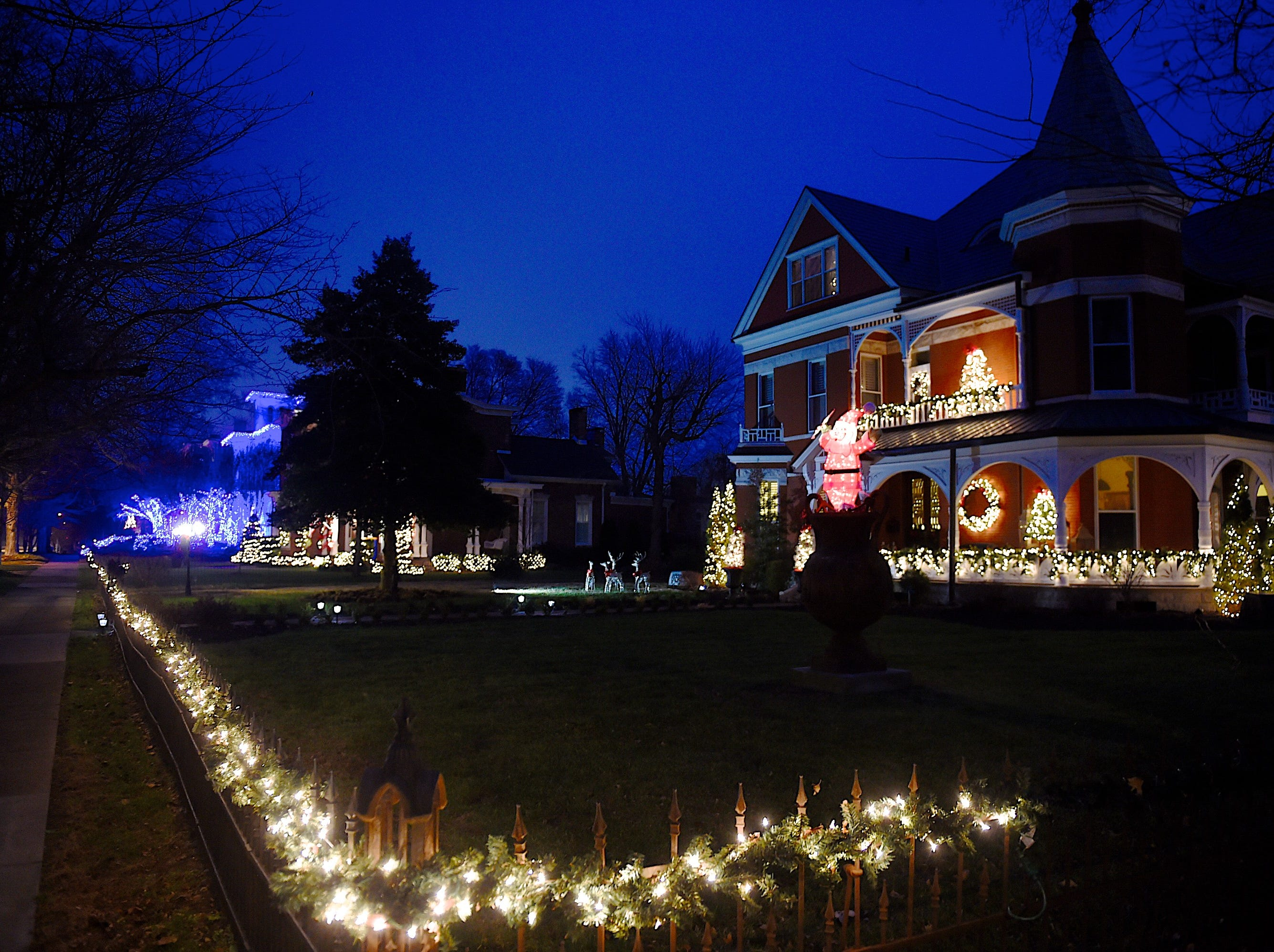 The Liles home on North Main (right) begins a row of historic homes decorated to the nines Tuesday evening, December 9, 2014.