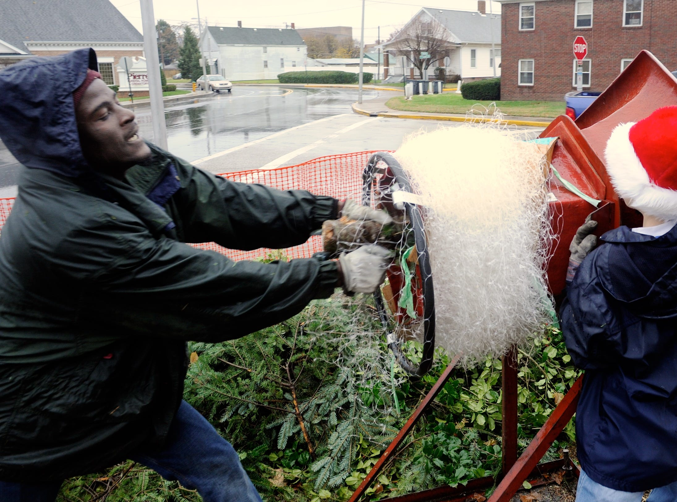Working in front of Sacred Heart Catholic Church, (L-R) Steeve Jean, Joseph Helfrich and Greg Mayer with Boy Scout Troop 399 struggle to push and pull a Christmas tree through a tree netter Saturday as the troop continues it's 61 year tradition, November 28, 2015.