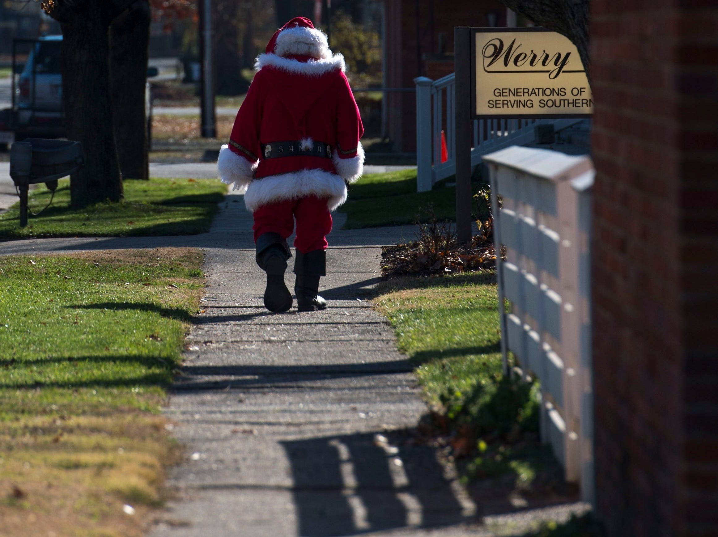 Santa Claus walks to his car at Christmas in New Harmony. The event included a craft market, musical performances, open houses at local merchants, and photos with Santa.