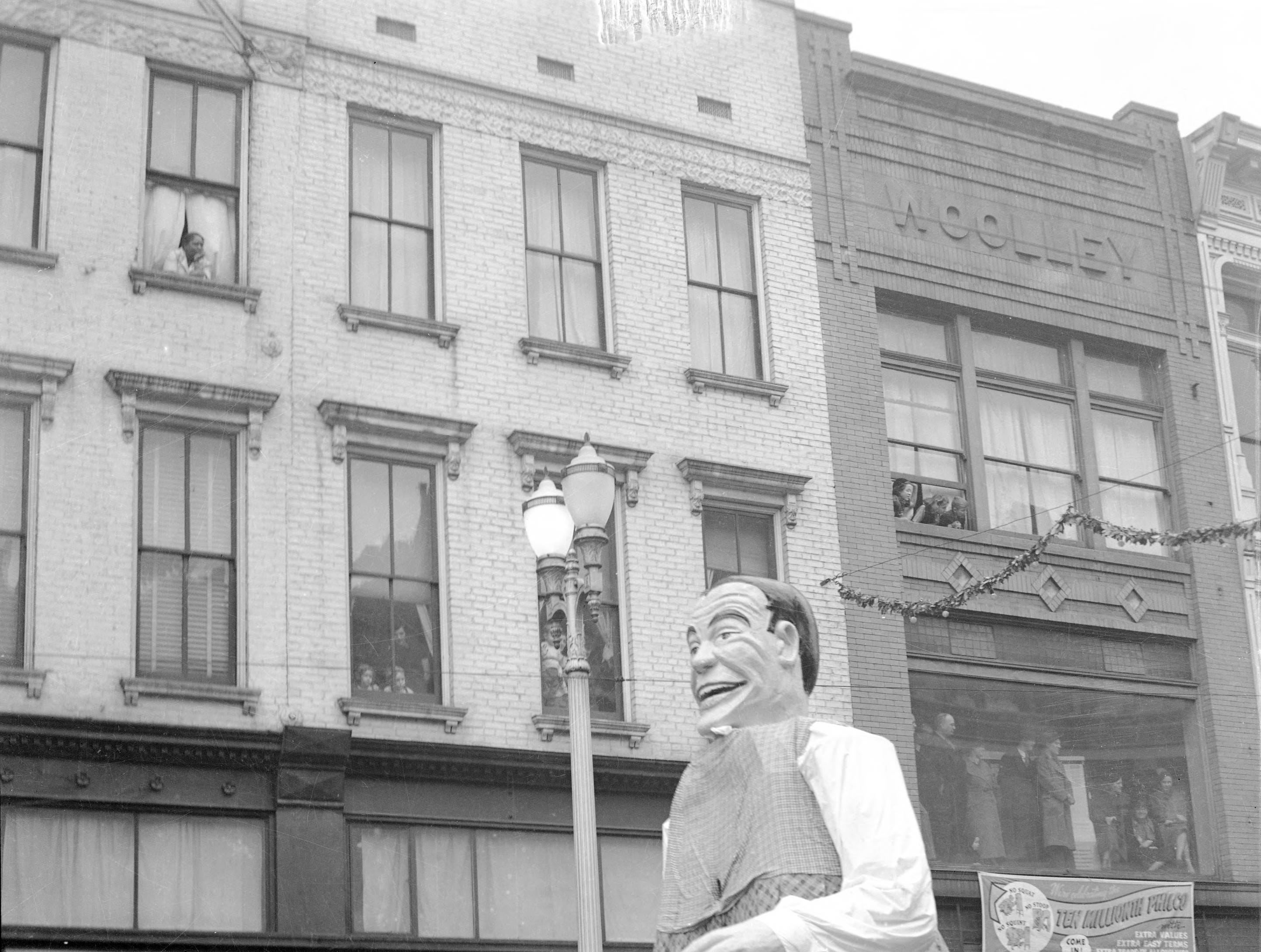 WPA Christmas Parade float--tall male figure, probably the King of Hearts, in front of piano store owned by D. Earl Dixon at 114 Main St in 1939.