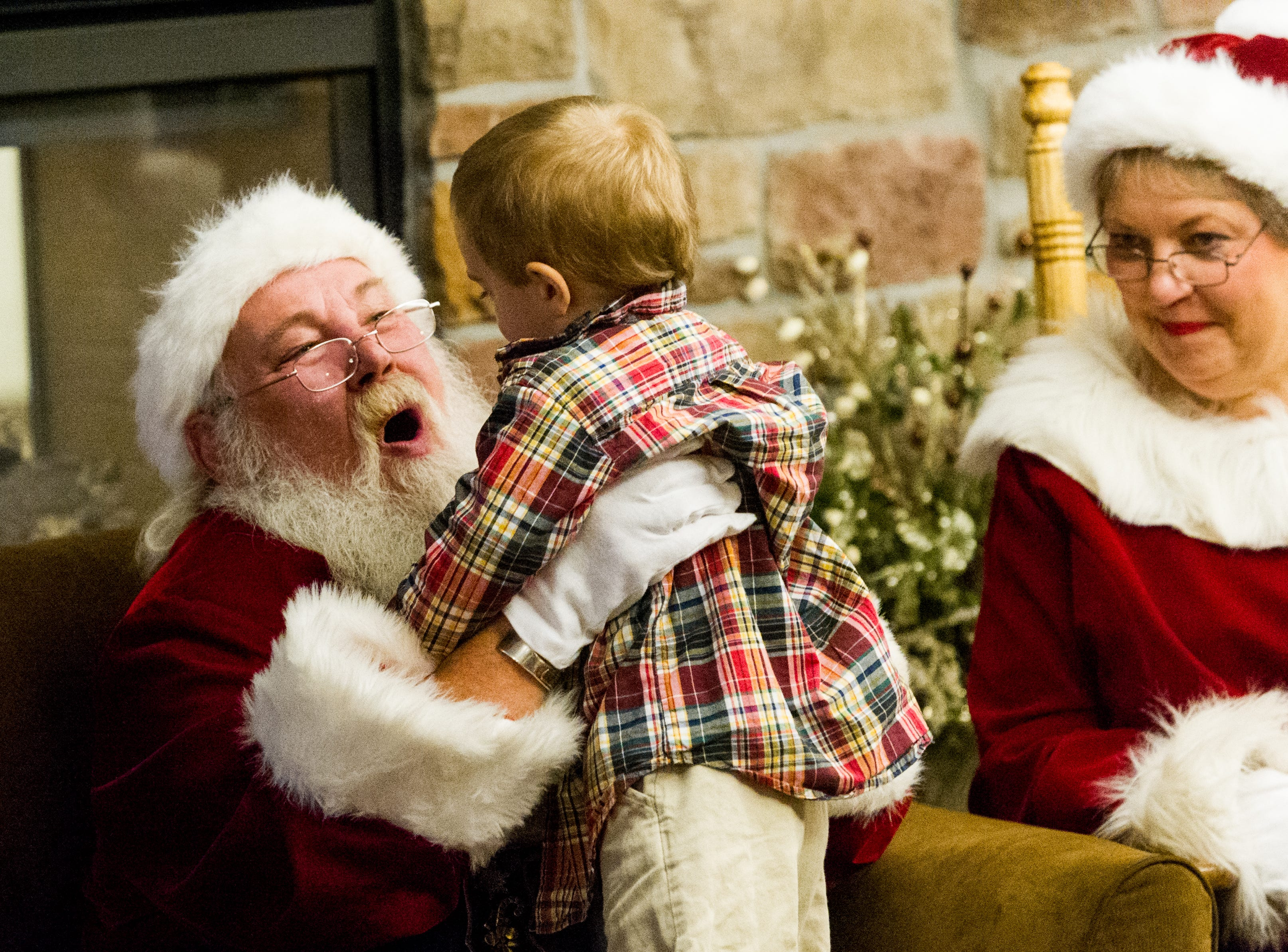 "DANIEL R. PATMORE / SPECIAL TO THE COURIER & PRESS ""Ho, ho, ho"" said Santa played by Rich Clarner as he lifts three year-old Hayden Sargent of Evansville, Indiana onto his lap as Mrs. Claus played by Linda Clarner looks on at the Ronald McDonald House Sunday Nov. 30, 2014 in Evansville, Indiana. Three years ago Hayden Sargent was in the NICU and his family stayed at the Ronald McDonald House."