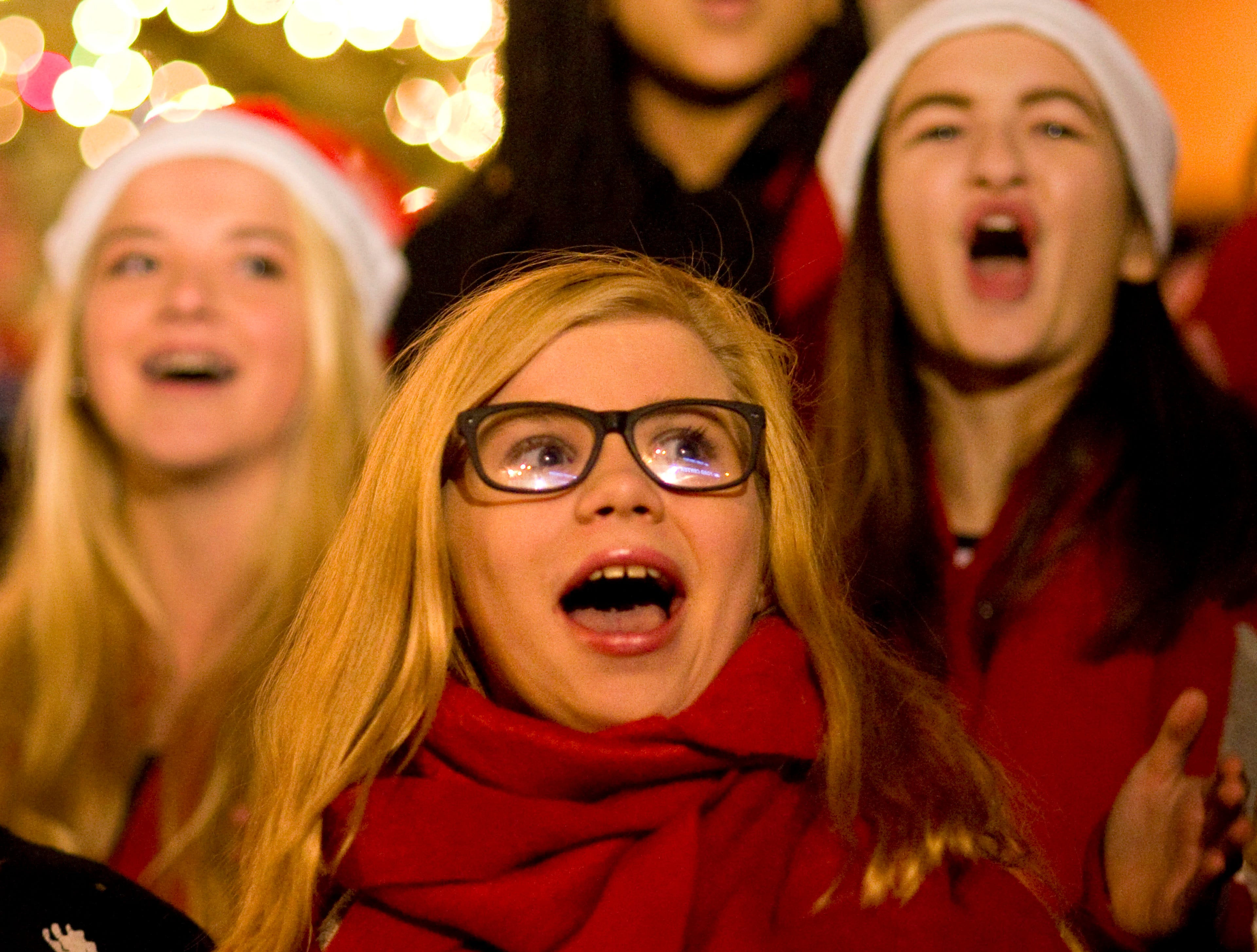 Shae Marks, 17, (center) sings at the tree lighting ceremony in front of the Civic Center with the Bosse High School and Reitz High School choirs Friday night. The tree, a 24-foot-tall blue spruce was donned with 12,000 lights.