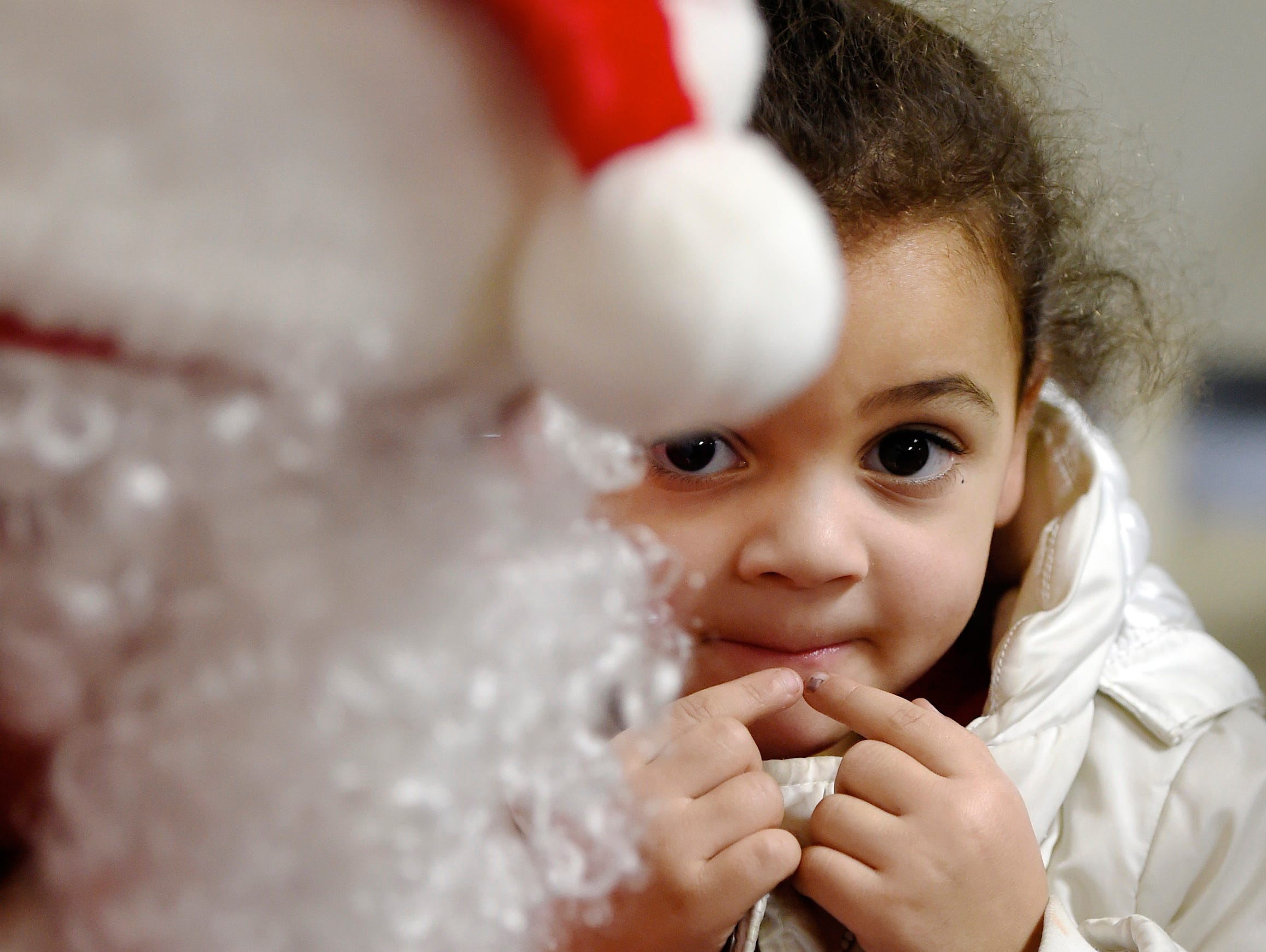 Taking her time, Rianna Burress, 4 years-old, doesn't seem quite sure what to tell Santa as she takes her turn on his knee during visit to a Christmas party for children living at the Ozanam Family Shelter. The party held at Saint Anthony Catholic Church was sponsored by the Mount Vernon-based Church of God's Mission.