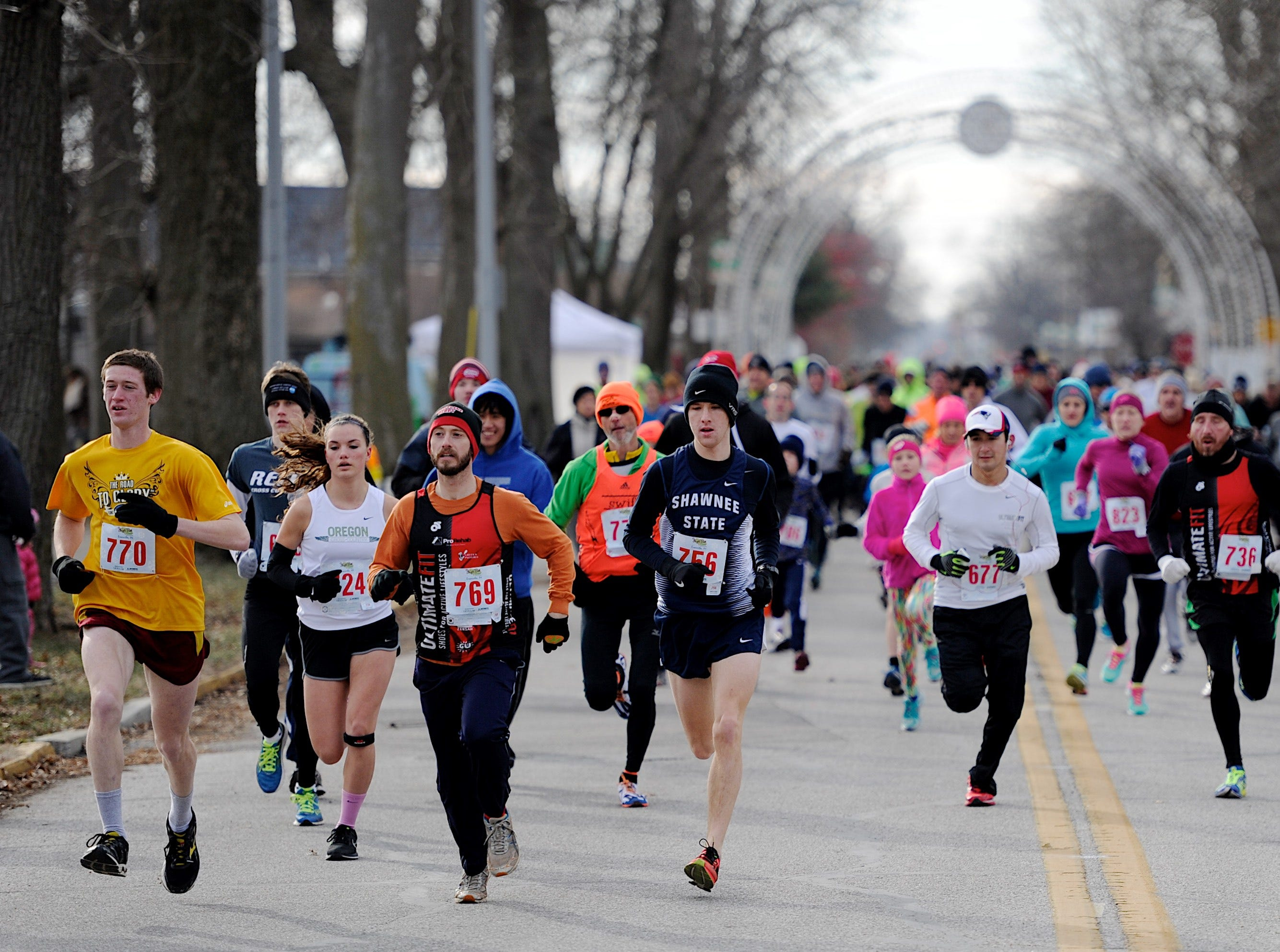 "Runners head in to the first turn as they begin the Day 1 Run 5K race at Garvin Park Thursday morning, January 1, 2015.  240 runners and walkers braved the 25 degree morning temperatures to participate in the race, which a portion of the proceeds will be donated to the family of Rebekah Shinabarge, who passed away Christmas morning.  ""We're trying to keep the tradition going,"" race director Jim Bush said of his company Rise Up and Run's taking over the race this year. He said they've had the race for years but this was the first year Rise Up and Run has organized it."