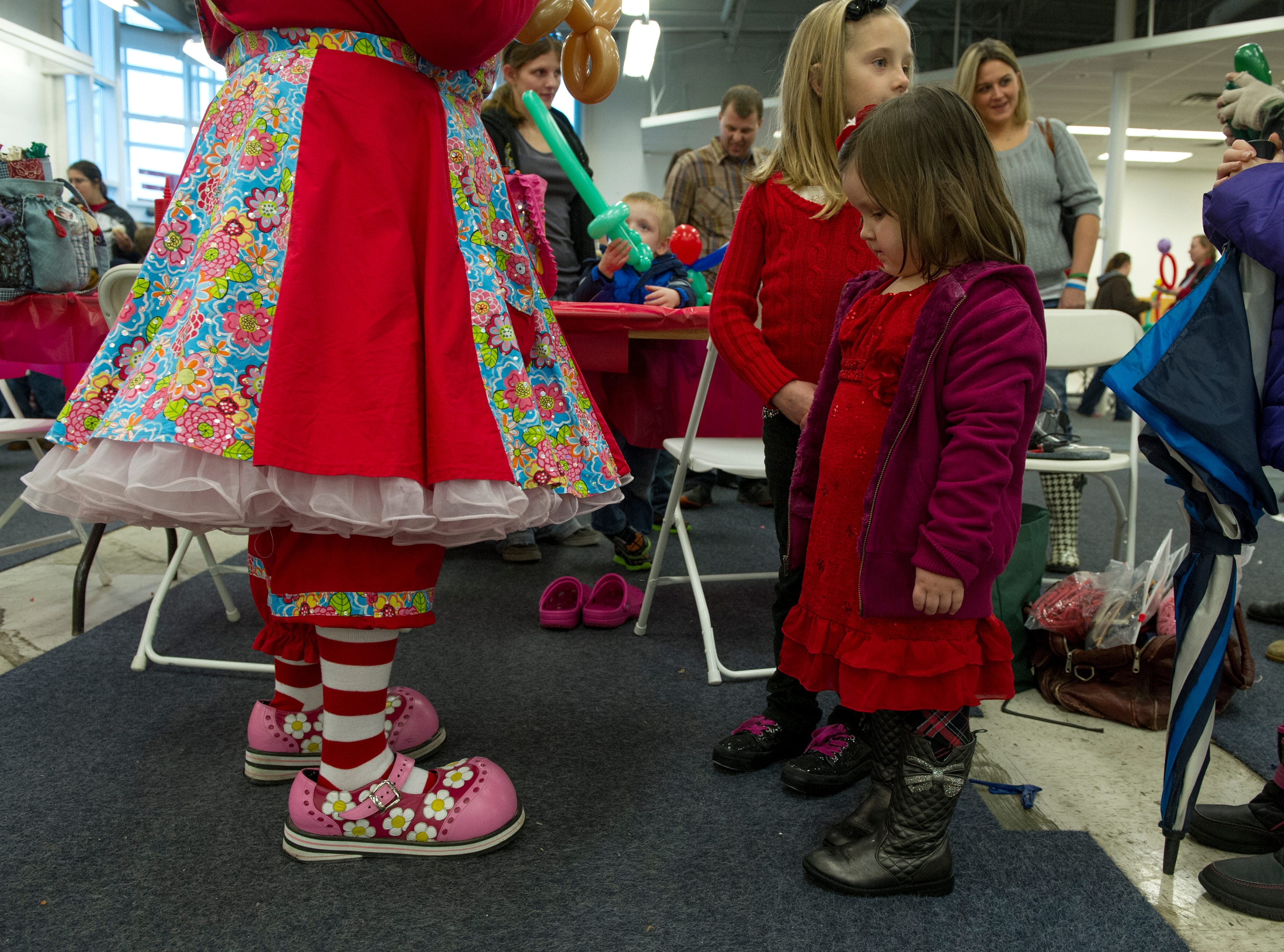 Marley Ochsner, 3, of Evansville scopes out Sparkles the clown and her giant shoes during Santa's Workshop put on by the organizers for the Christmas on North Main parade held inside the old CVS on Main Street in Evansville Sunday Nov. 23, 2014. The parade was cancelled due to rain.