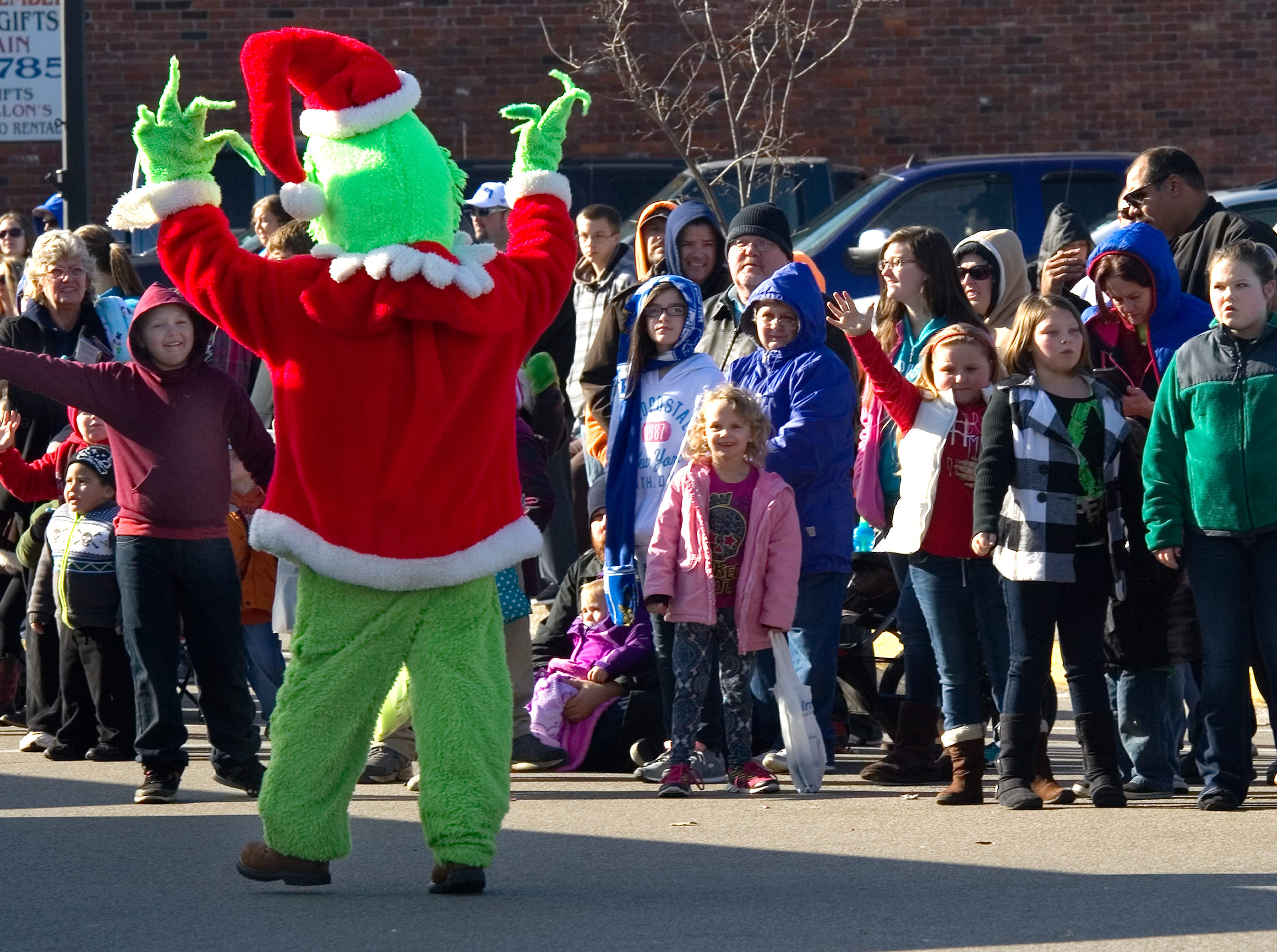 The Grinch, one of the costume characters from Evansville's West Side Nut Club that entertained the crowd, draws different reactions from those lining Main St. during the annual Christmas Parade in Henderson, Ky. on Saturday morning, Dec. 5, 2015.