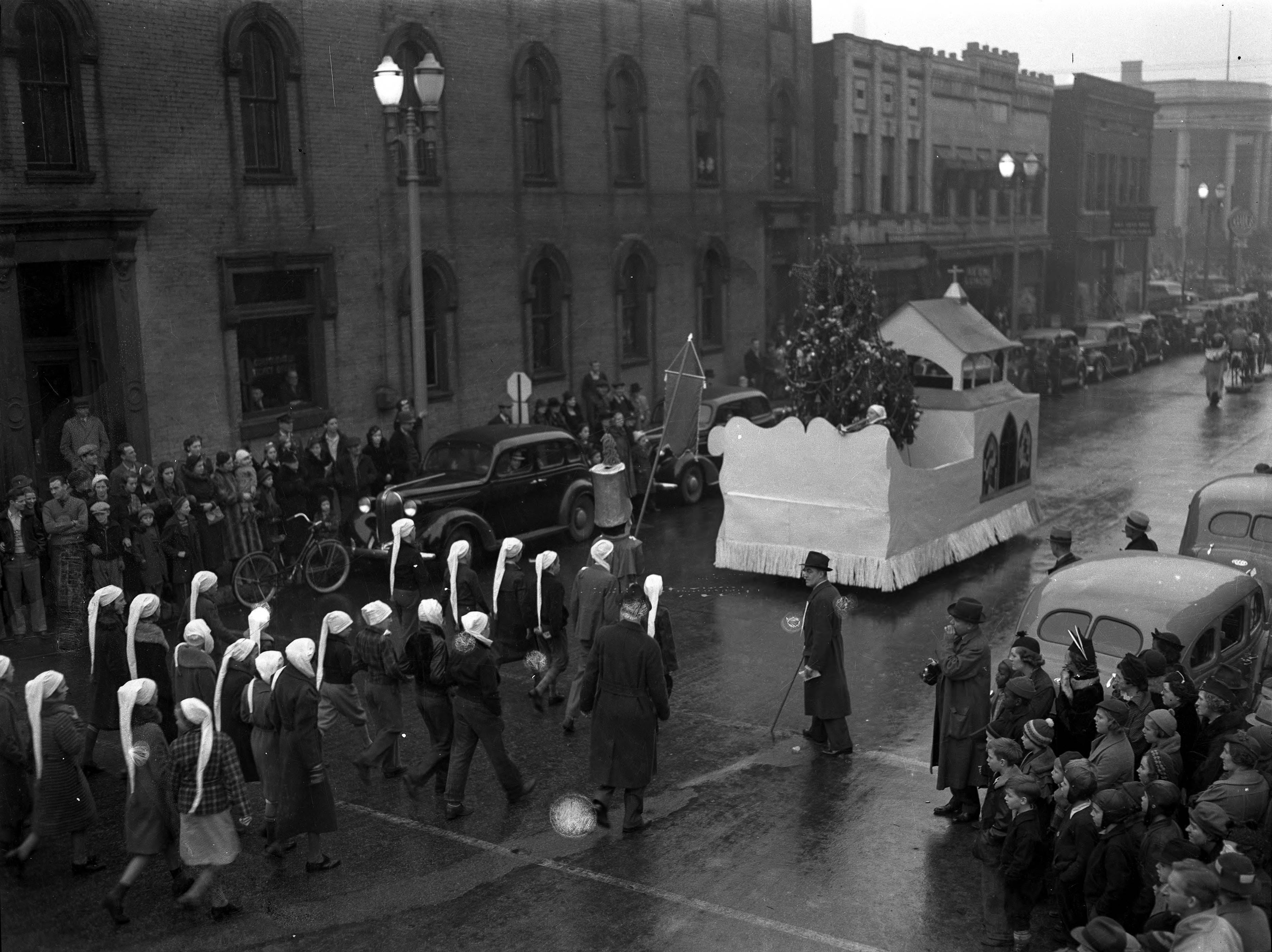 WPA Christmas Parade float--people wearing long stocking type caps following a church float, said to be on Main St. Crowds and cars nearby.