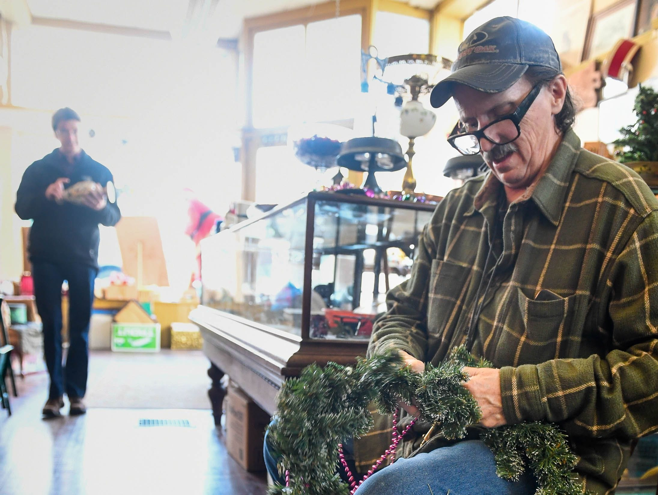 Scott Lauderdale untangles some Christmas decorations at the Country Gentleman Antique store during the Newburgh Celebrates Christmas event.