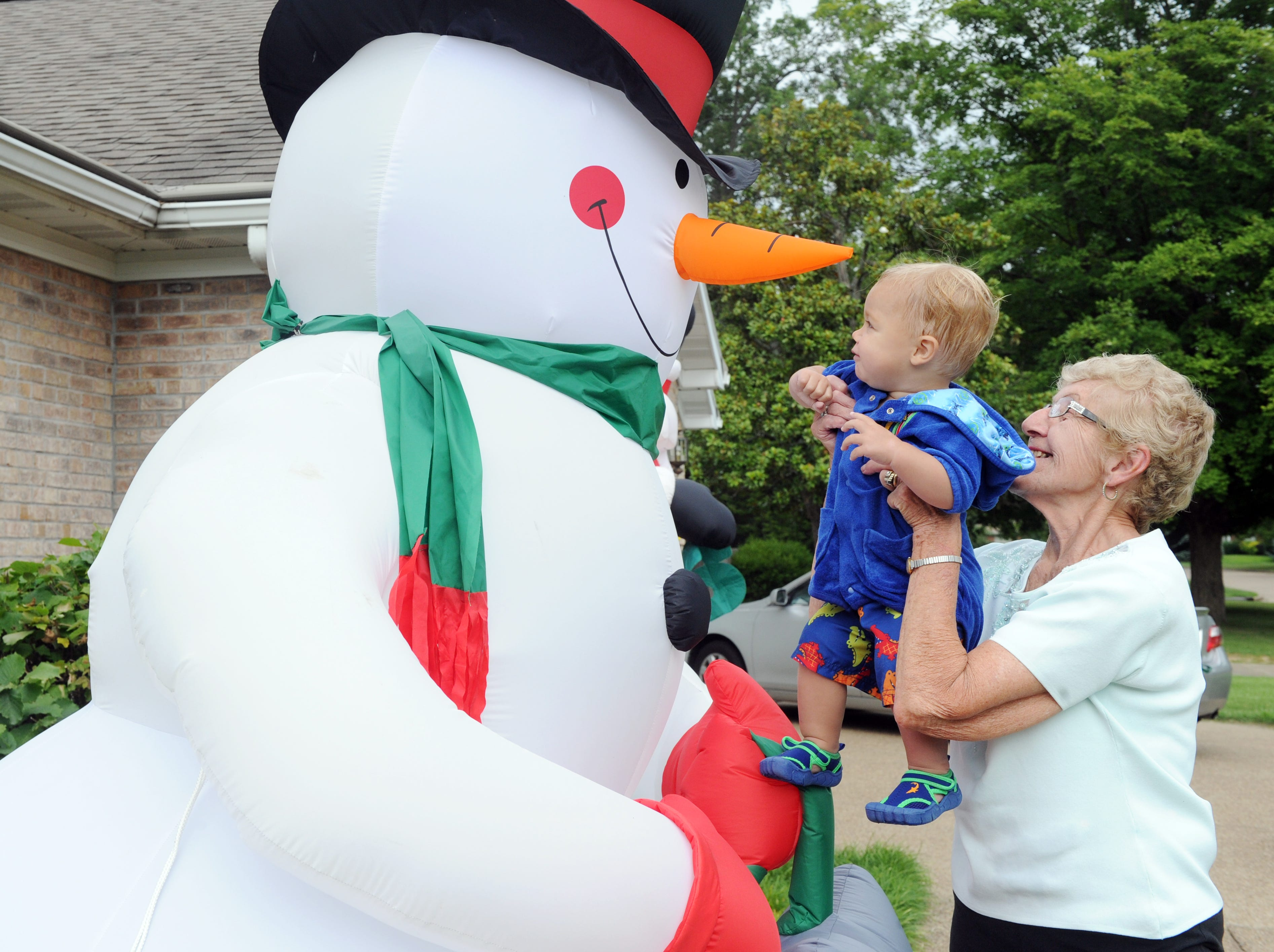 Rita Durnin lifts her great grandson, Trent Oeltjen, 16 months, up to see the inflated snowman outside Rita's house after swimming in the pool on July 19, 2014. Because Rita's children  and grandchildren live in New York, California, Iowa, Wisconsin and Minnesota getting together for the holidays is not possible, so two years ago they started celebrating Christmas in July and enjoying family time in June. Rita sets up some of her decorations both outside and inside for her great grandchildren to enjoy.