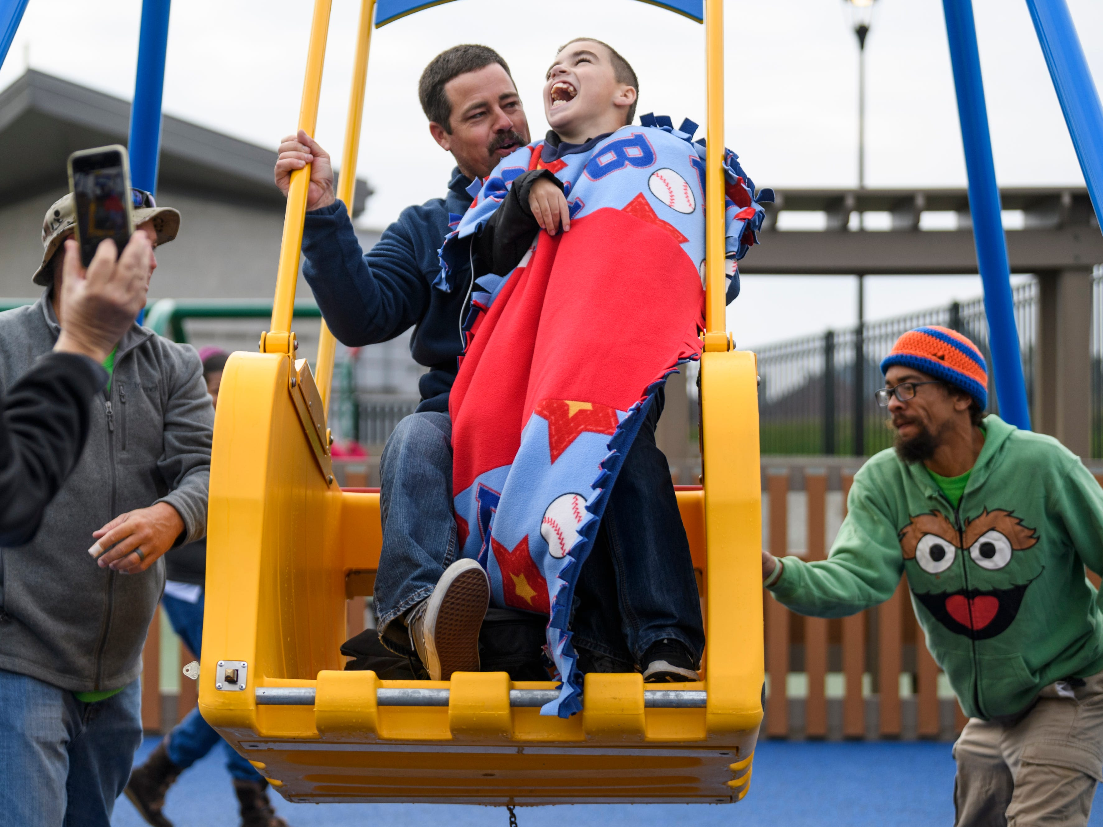 Dan Masterson, center left, and his son Roman Masterson, 11, center right, test out the Liberty Swing, which allows disabled children to hook their wheelchairs into the platform, at the new Mickey's Kingdom playground in downtown Evansville, Ind., Saturday morning, Oct. 27, 2018. The swing was made and shipped from Sydney, Australia.