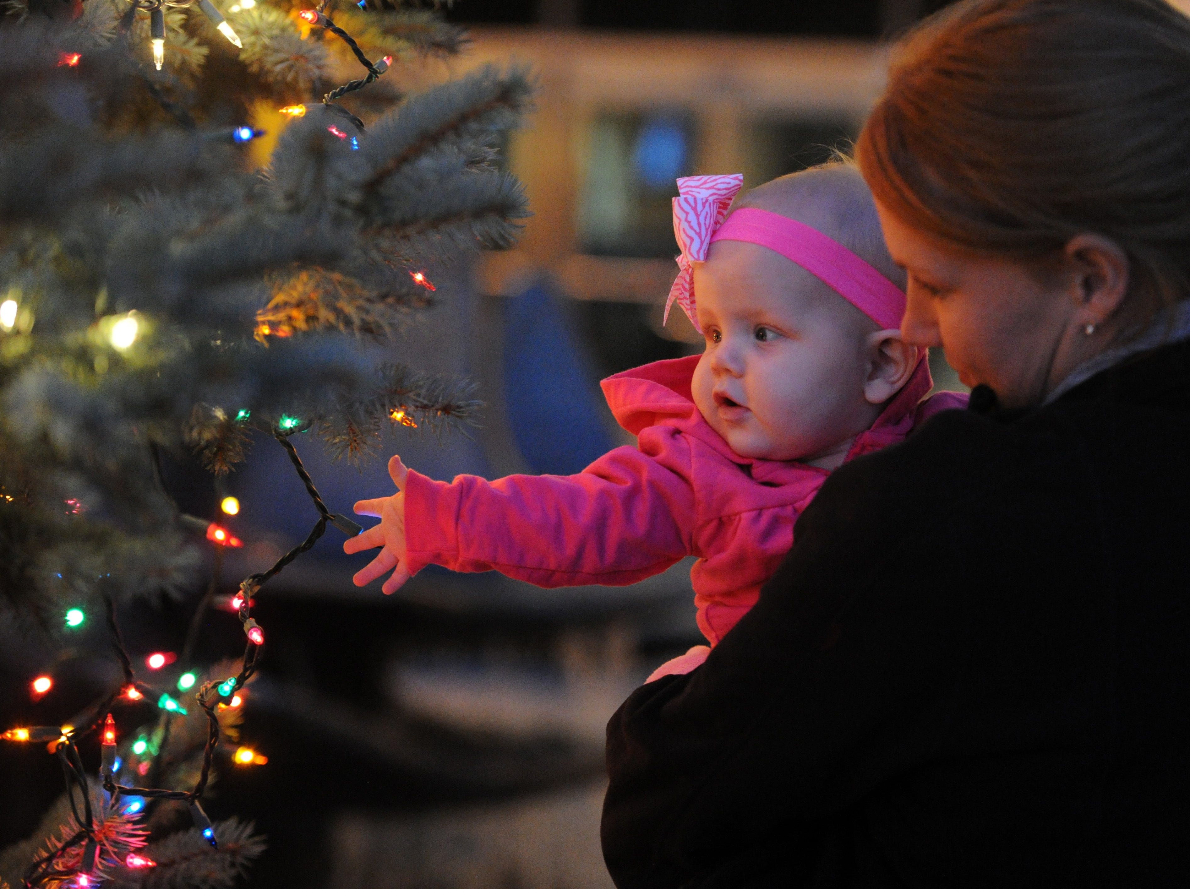 Whitley Brendel, 7-mos., checks out some of the illuminated lights with the help of her mother Casey Gardner after a Christmas tree lighting ceremony was held in front of the Civic Center Wednesday.  The tree was donated by Florence Murphy of Evansville and is decorated with about 6,100 lights.