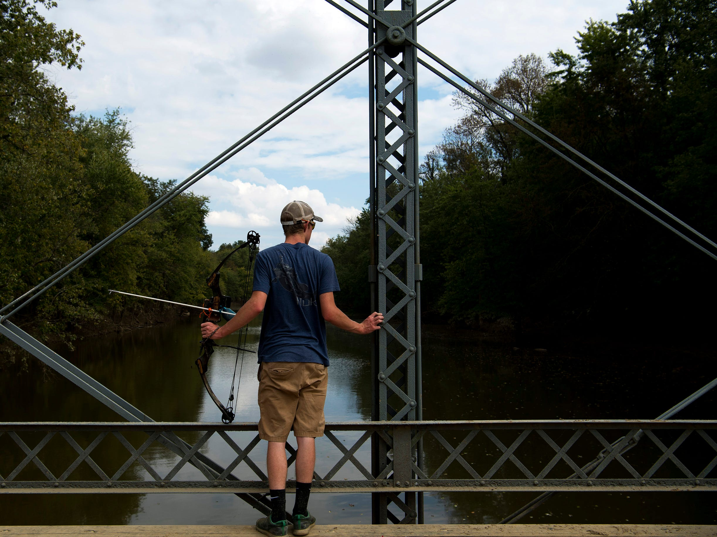 Jarrett Sandage, 17, a Boonville High School student, searches for carp with his bow and arrow above Little Pigeon Creek near Yankeetown, Ind., Monday afternoon, Oct. 8, 2018. The bridge is a hot spot for local bow fishermen recently had about 30 archers perched atop the wood and steel structure.