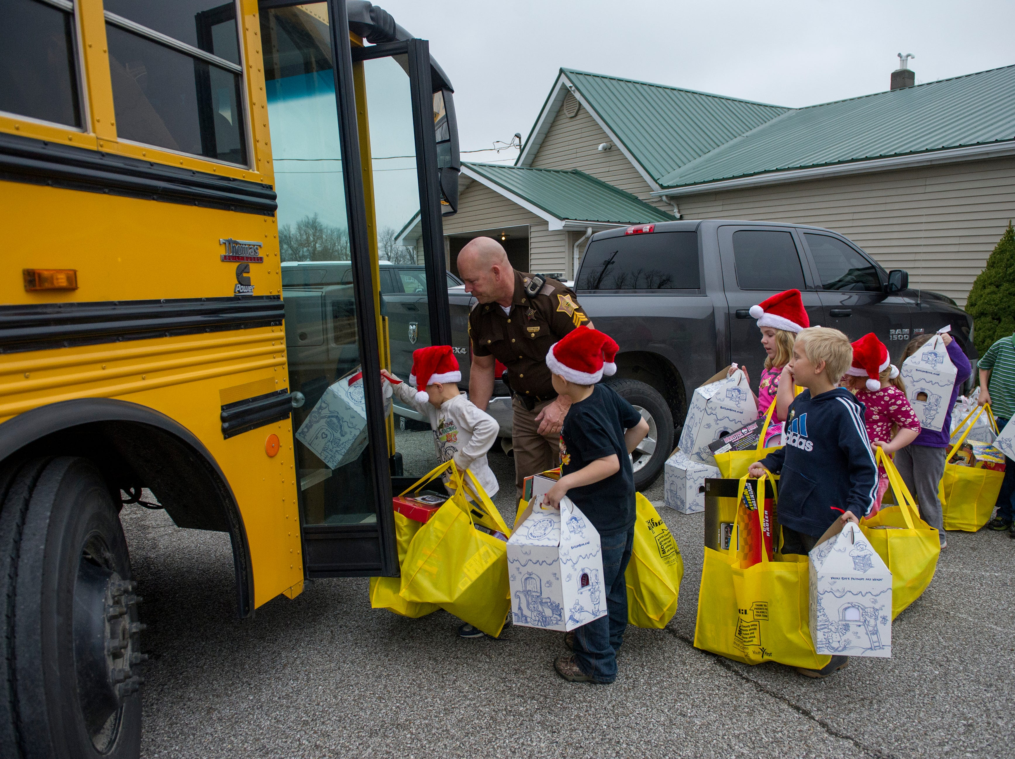 Sargent Scott Whitlow helps students back on the bus with arm loads of toys after the Warrick County Police Department Christmas Party in Booneville Tuesday Dec. 9, 2014. The deputies held fundraisers and took donations from the community to raise money to buy gifts for at risk elementary school children in the county.