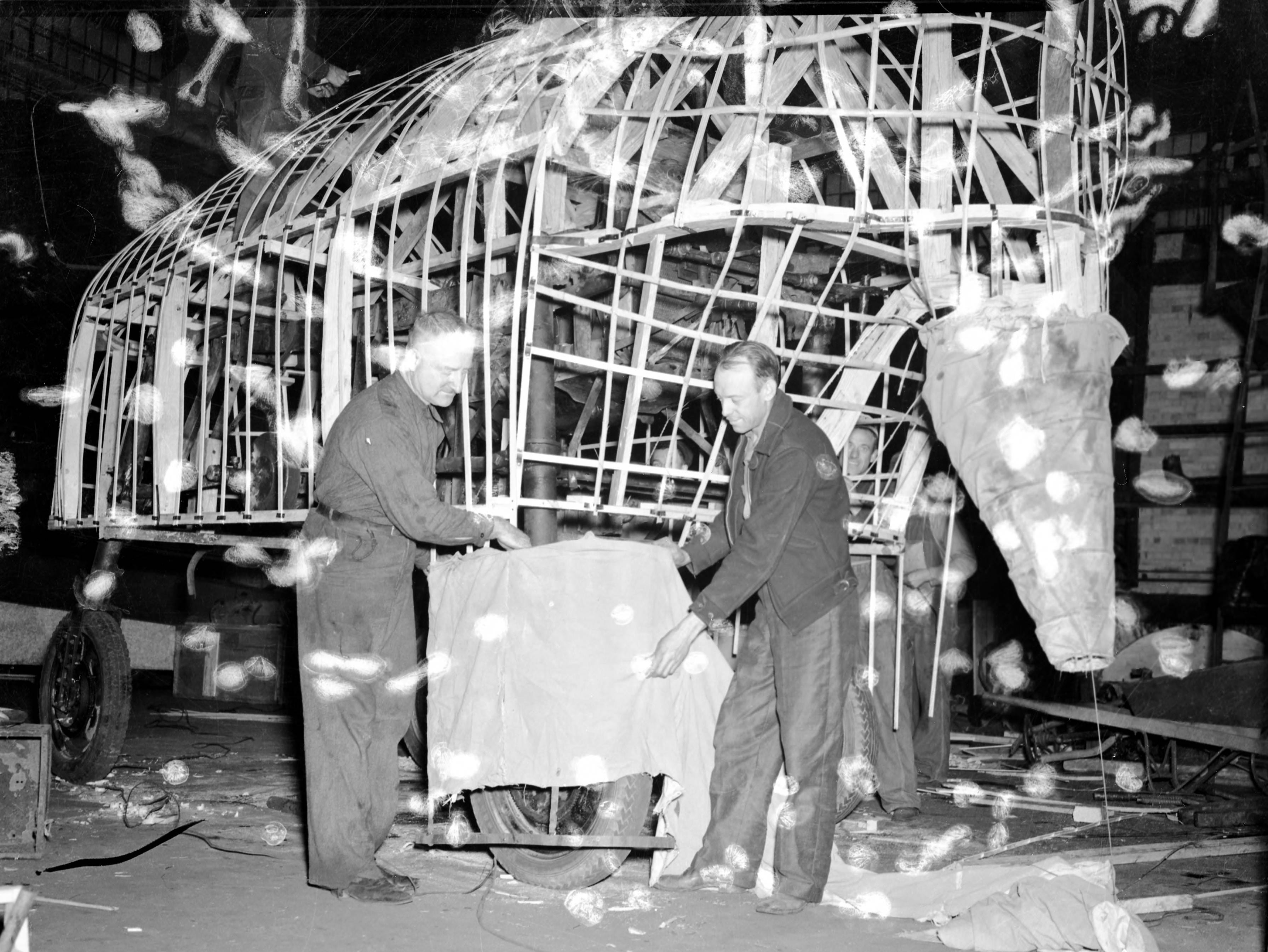 Two men working on a float for the WPA Christmas parade.  Only the frame and the beginning of the covering has been completed.
