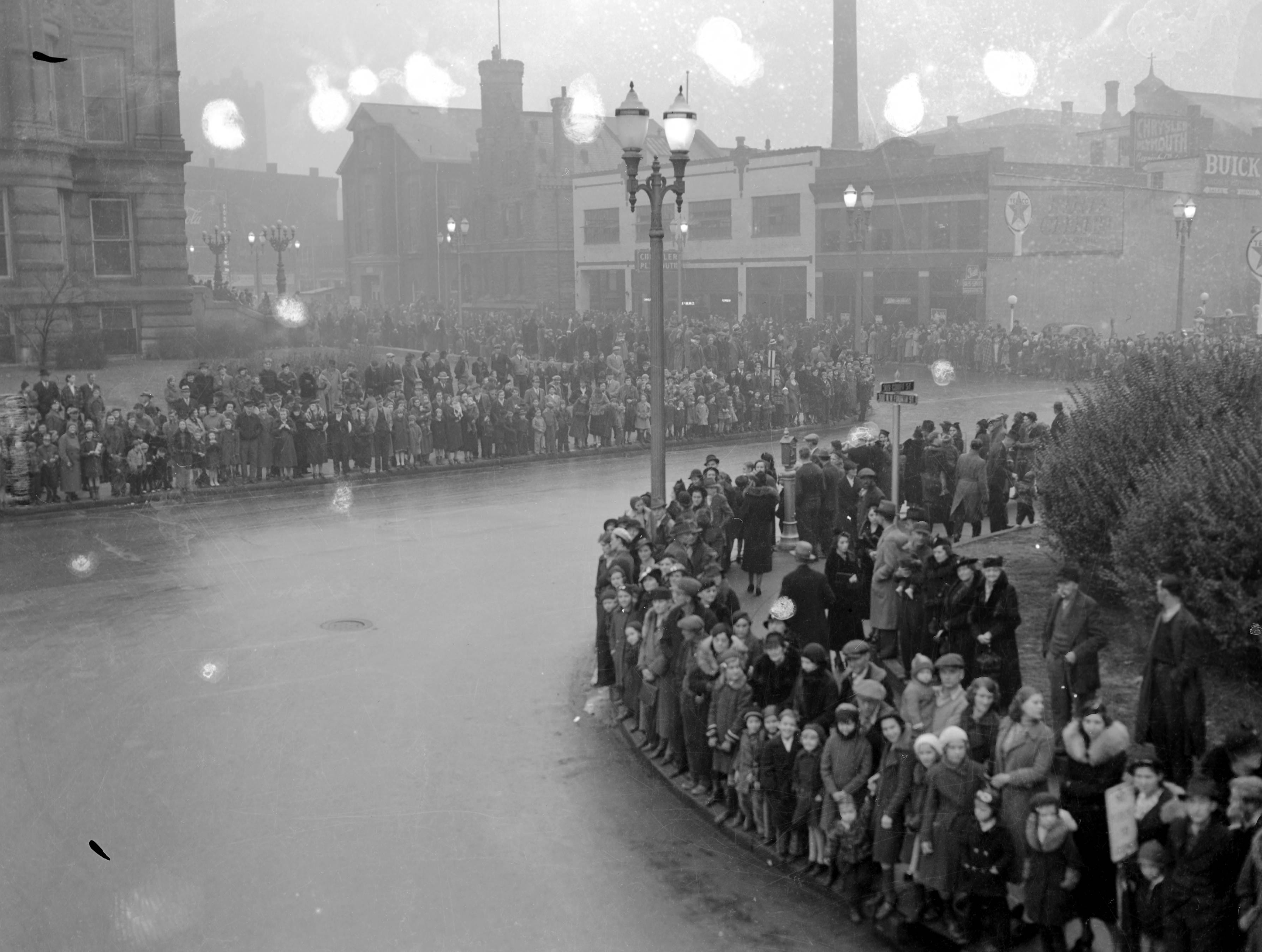 Crowds awaiting WPA Christmas parade at Court St. and NW 4th St.  The large building on the left is the Vanderburgh County Court House and across the street is the Lincoln Motor Co. (they sold Buicks) at 218 NW 4th St.