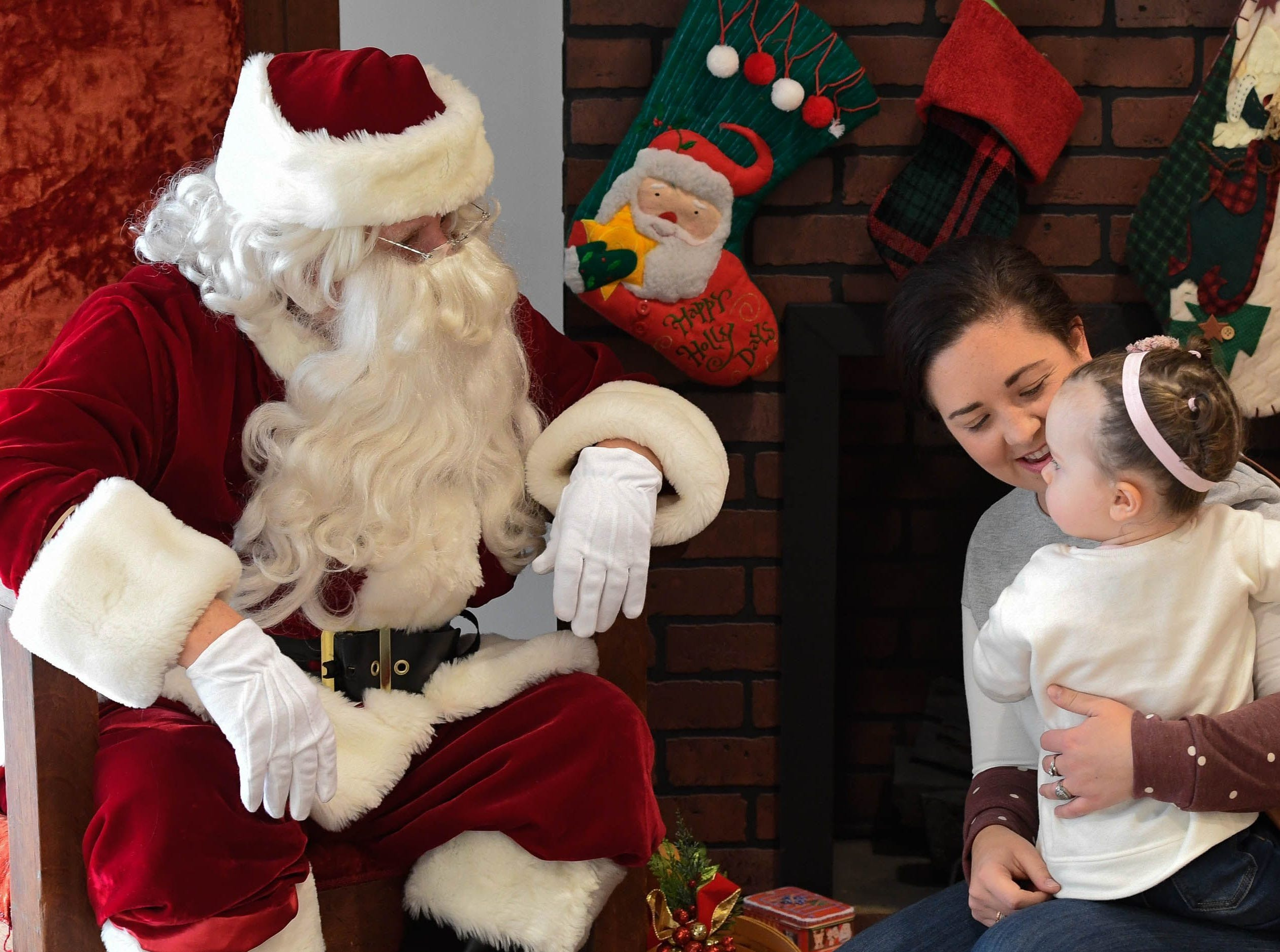 Sarah Brooks with her daughter Stella, 22 months-old, visit with Santa.