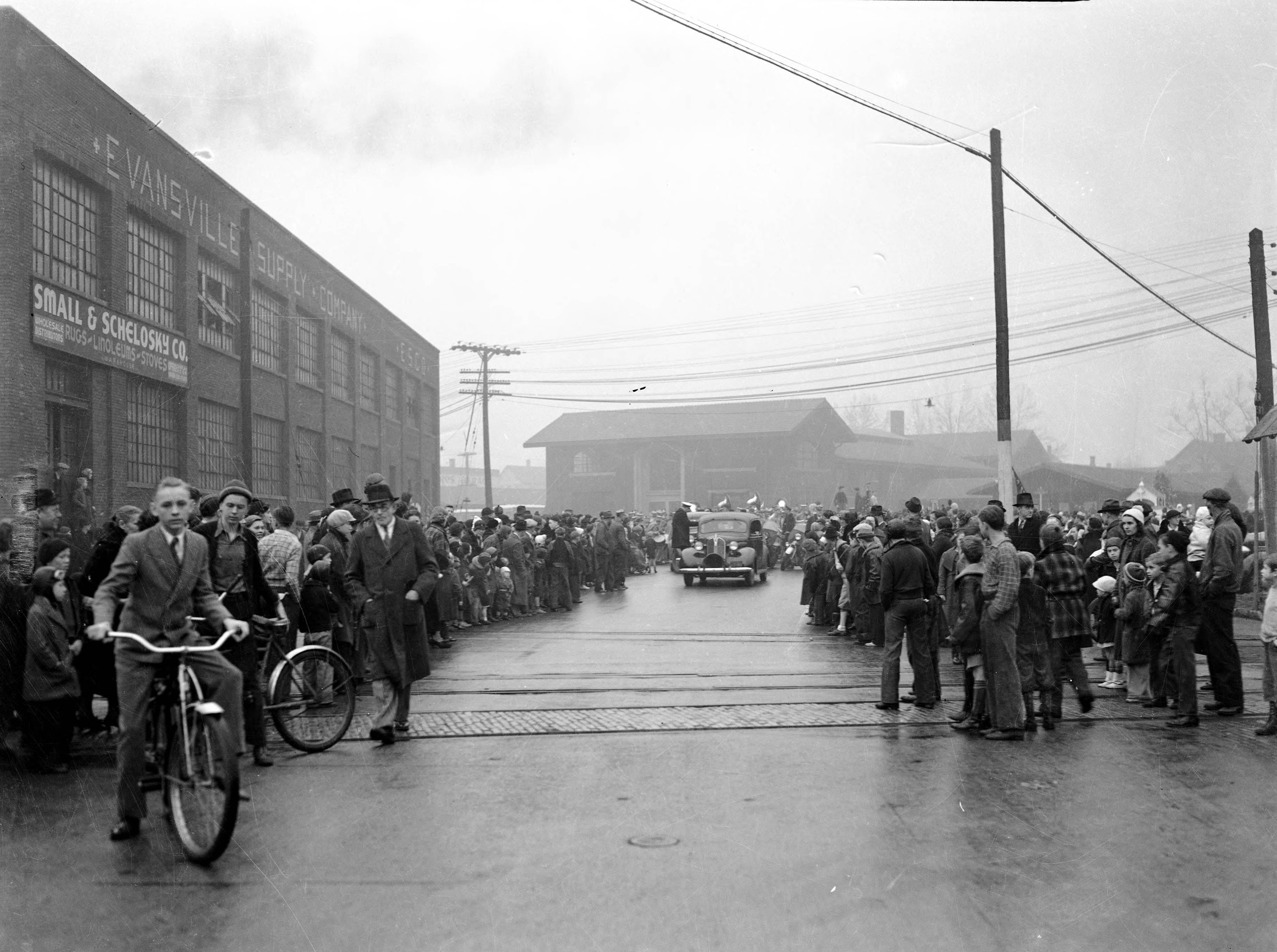 Crowds awaiting WPA Christmas Parade, standing in front of Evansville Supply Co. at 800-14 Pennsylvania St.  This appears to be the beginning of the parade, with lead car, motorcycles, and a band in the mid-background in 1939.