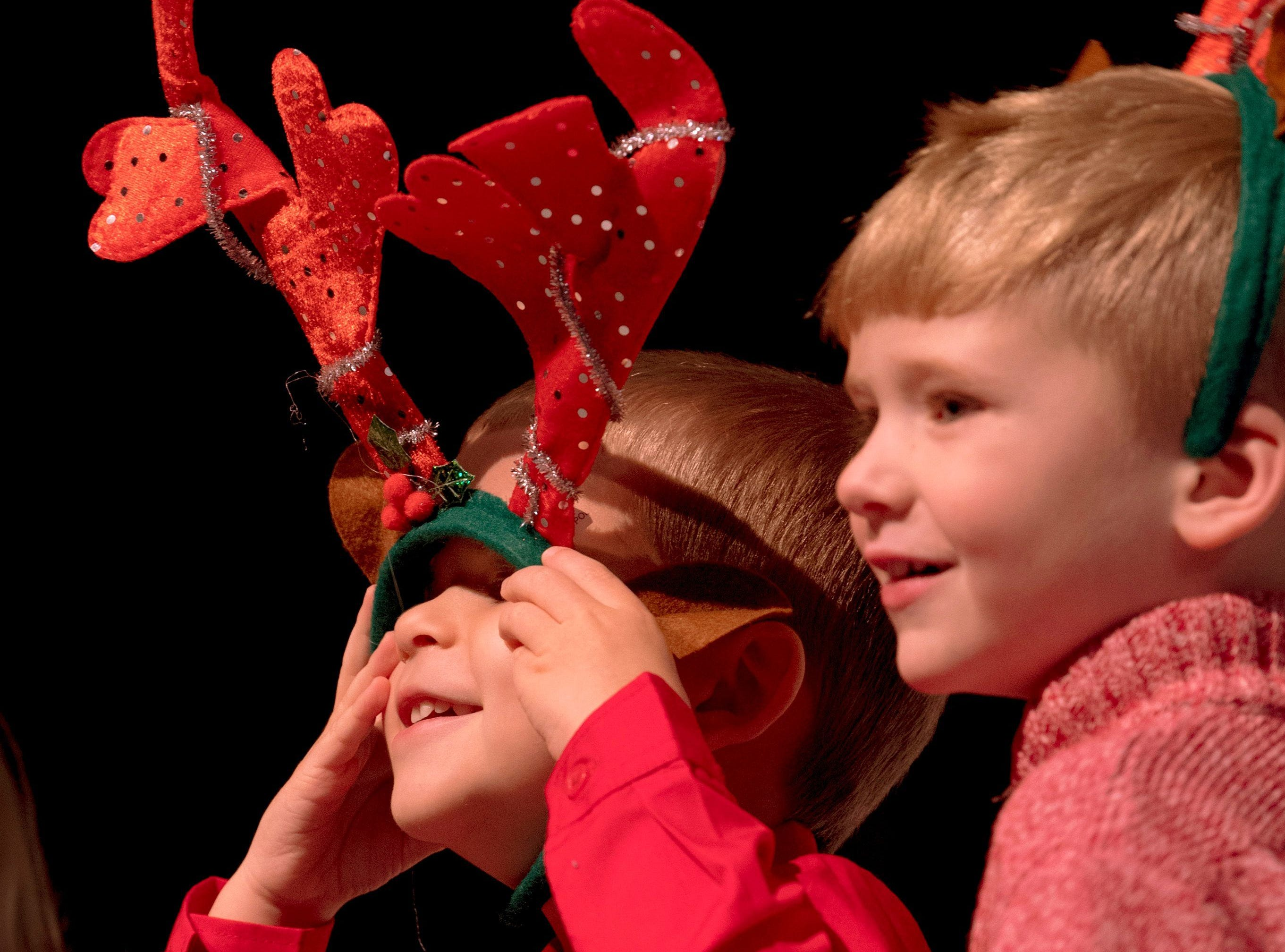 Zakary Tischhauser, left, wrestles with his antlers as he and his class, including Deacon Stone, right, perform.