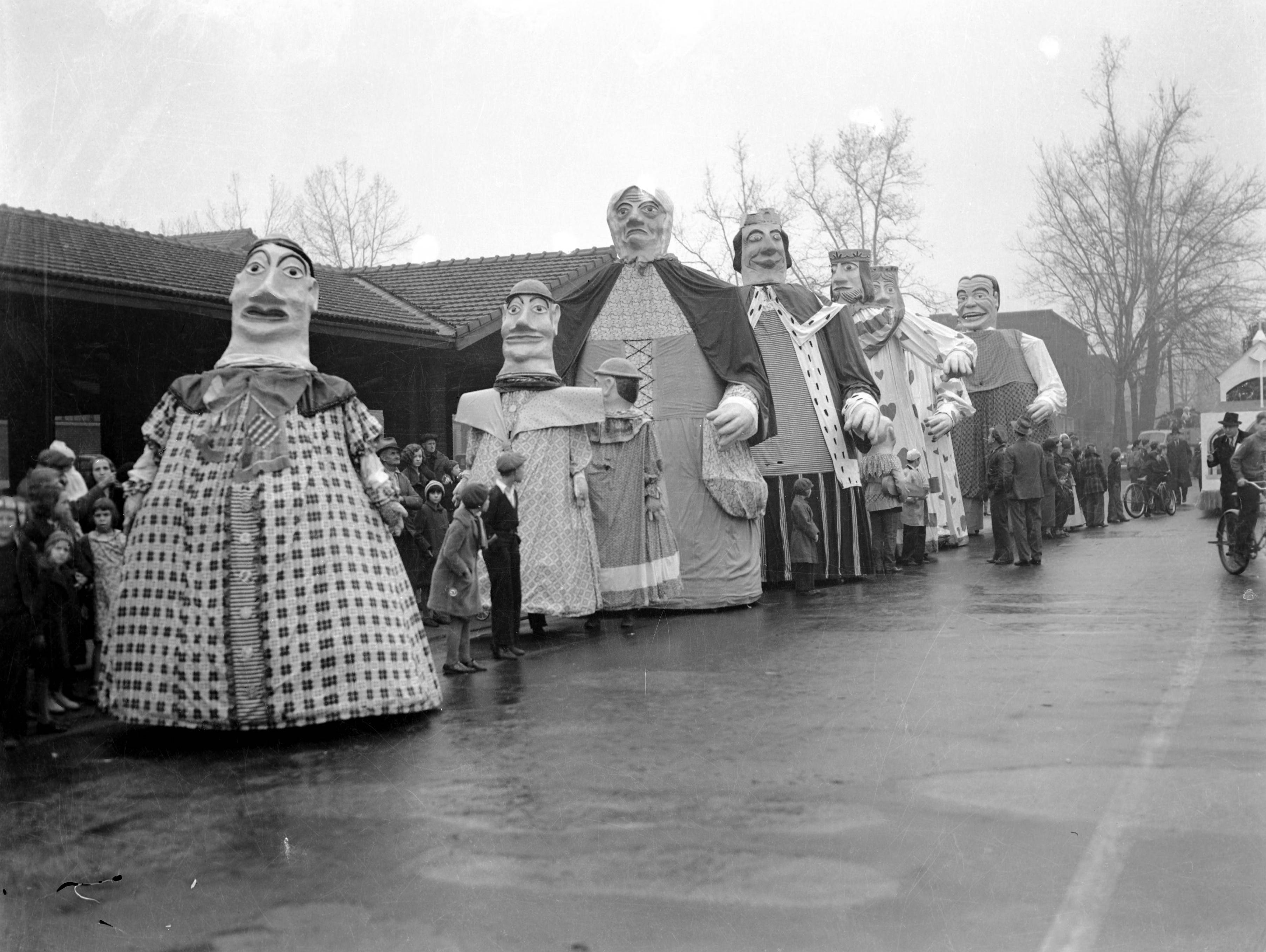 WPA Christmas Parade floats--7 tall figures lined up, Jack-in-the-Box figure, with children on street among figures, and man with cane possibly directing the parade.  Crowd on sidewalk watching.  This is probably taken at the Municipal Market at 813 Pennsylvania St., side entrance at 814 W. Indiana St. (not sure which side shown) in 1939.