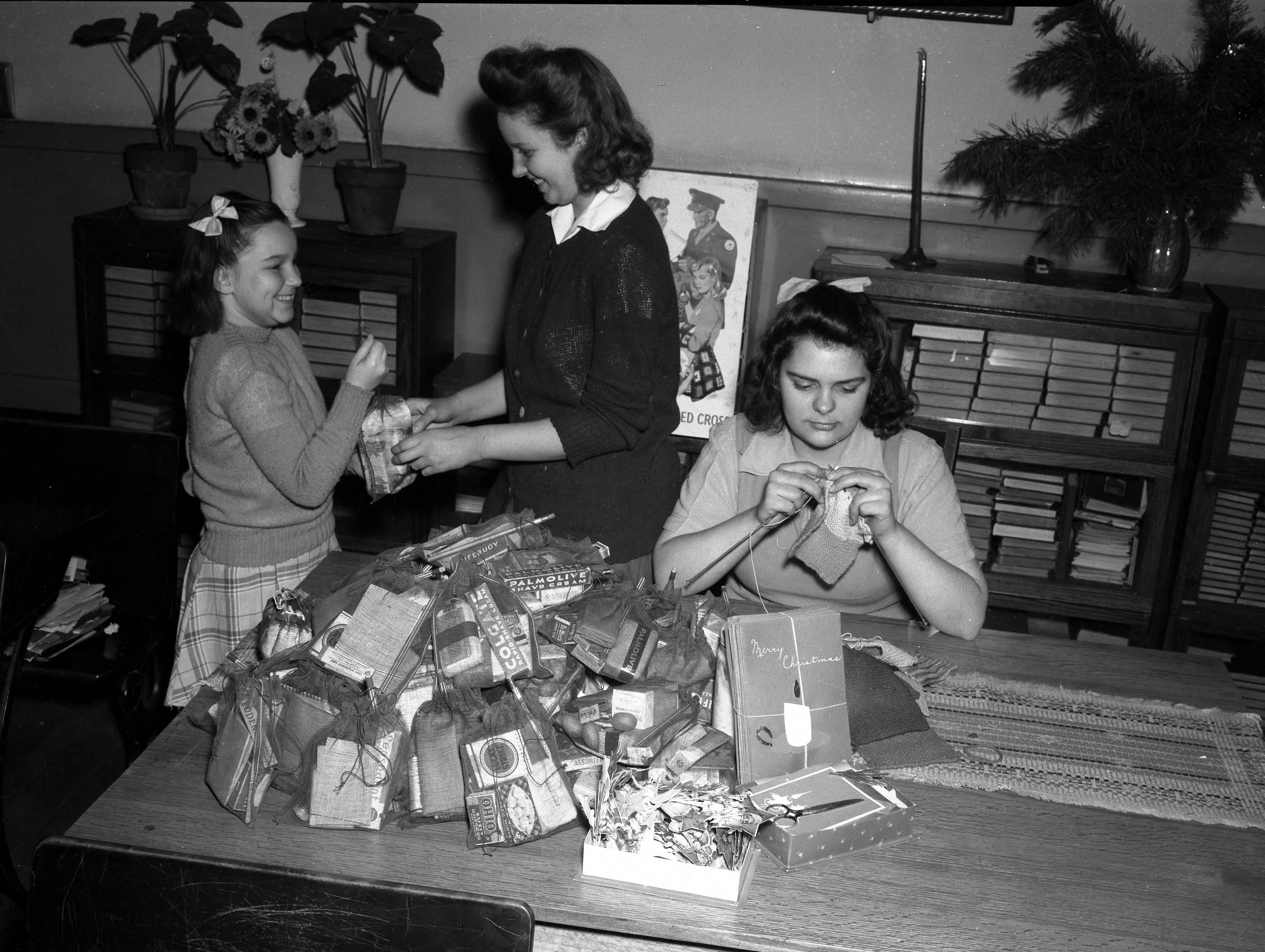 "Girl knitting at a table with woman helping another girl """"wrap"""" a package.  On the table is a pile of sheer cloth bags with soap, shaving cream, cigarettes, matches, gum, pencils, cough drops, toothpaste, etc., and a stack of Christmas cards nearby.  There is an American Red Cross poster on the wall, and behind the table are lawyers bookcases with books stacked inside in 1945."