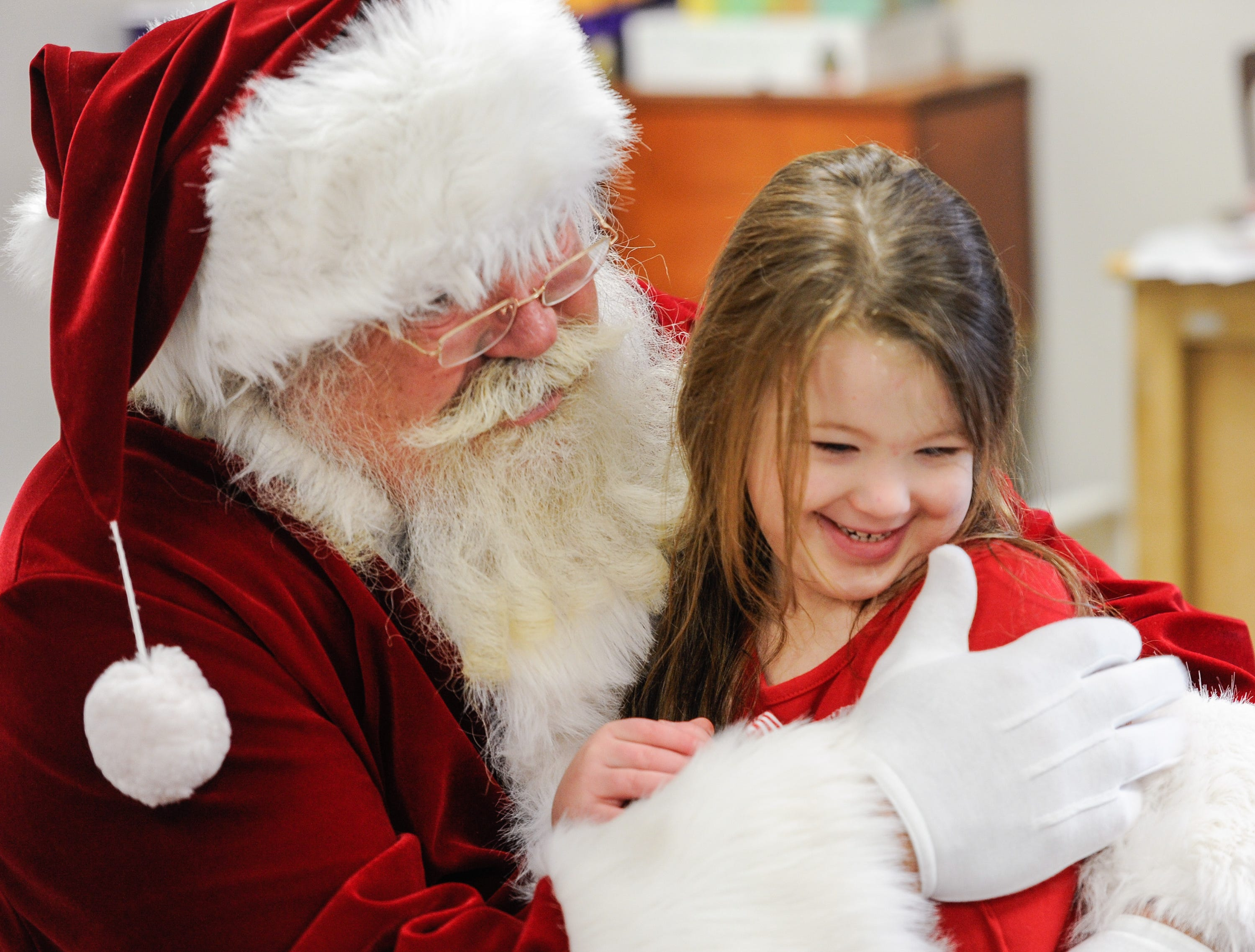 Clara Cater, 5, receives a hearty hug from Santa as he visits the preschool kids at the Easter Seals Rehabilitation Center in Evansville Tuesday morning, December 22, 2015.