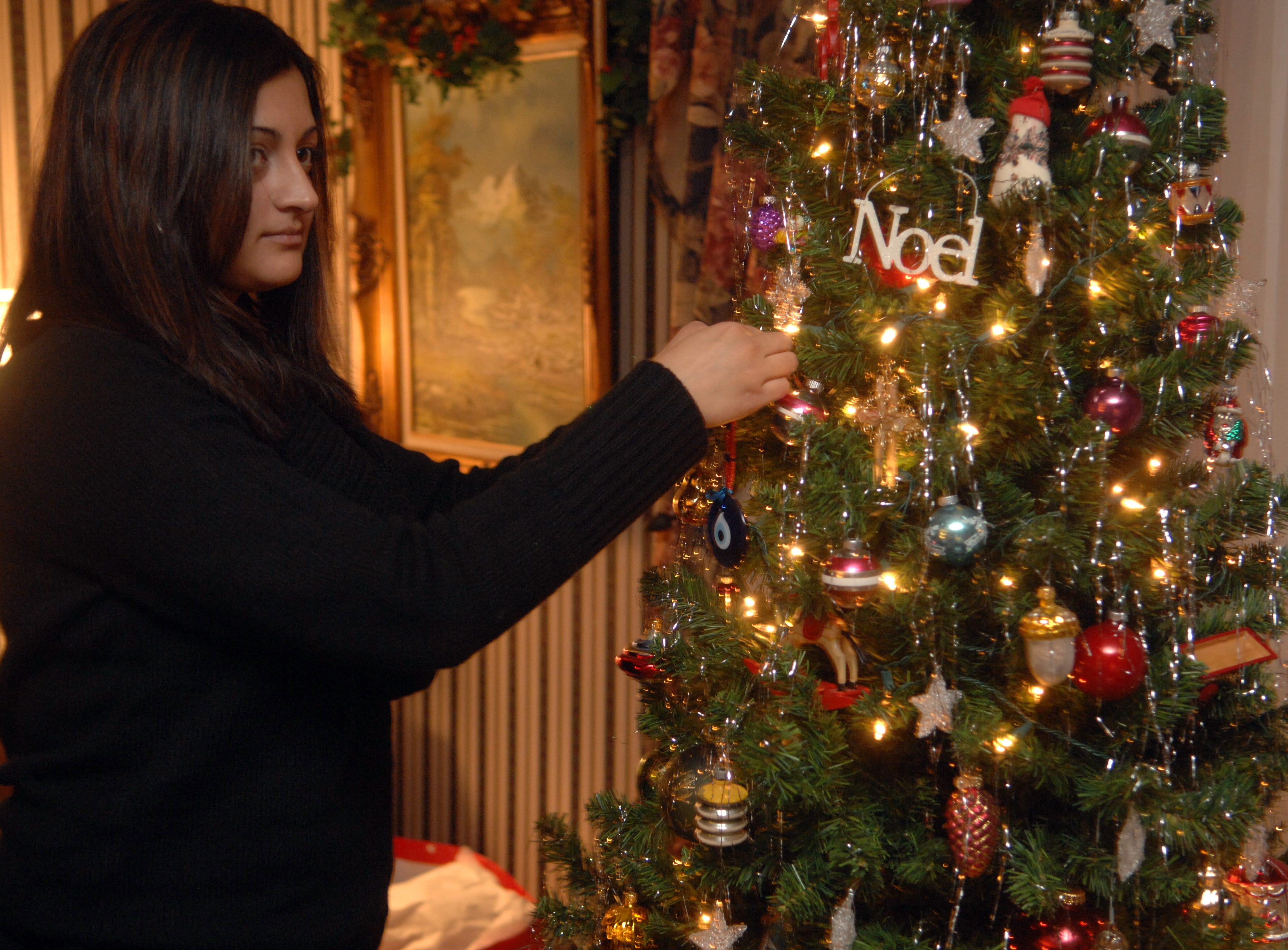 Gul Akyel of Canakkele, Turkey adds her special ornament to Carol Houston's Christmas tree at Carol Houston's home in Evansville recently.  Houston opens her home to share Christmas with international students from UE and USI each year.