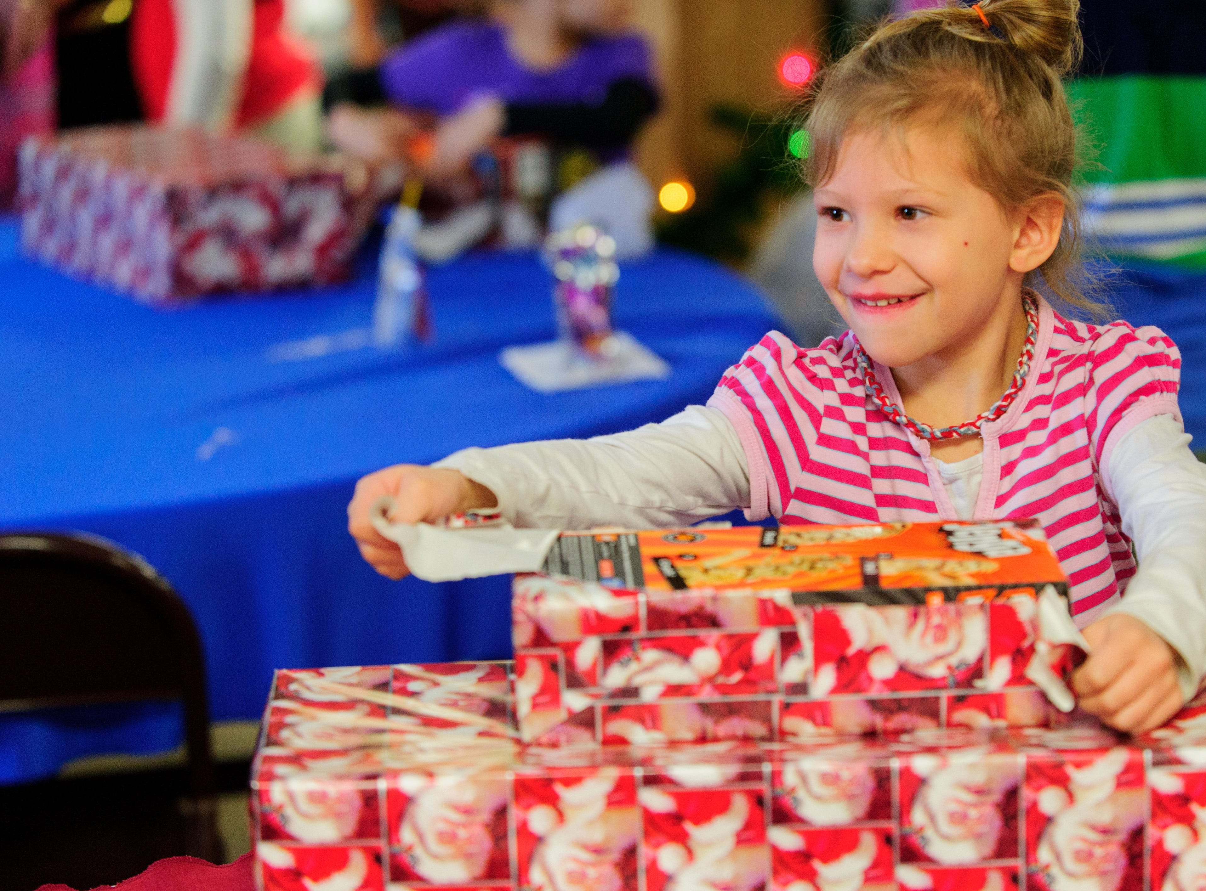 Candice Nau, 5, unwraps one of her presents from Santa at the annual FOP Christmas party at FOP Camp on Happe Road on Evansville Northwest side Saturday morning Dec. 14, 2013. For close to 50 years the FOP has been have Christmas party for Evansville's needy children.