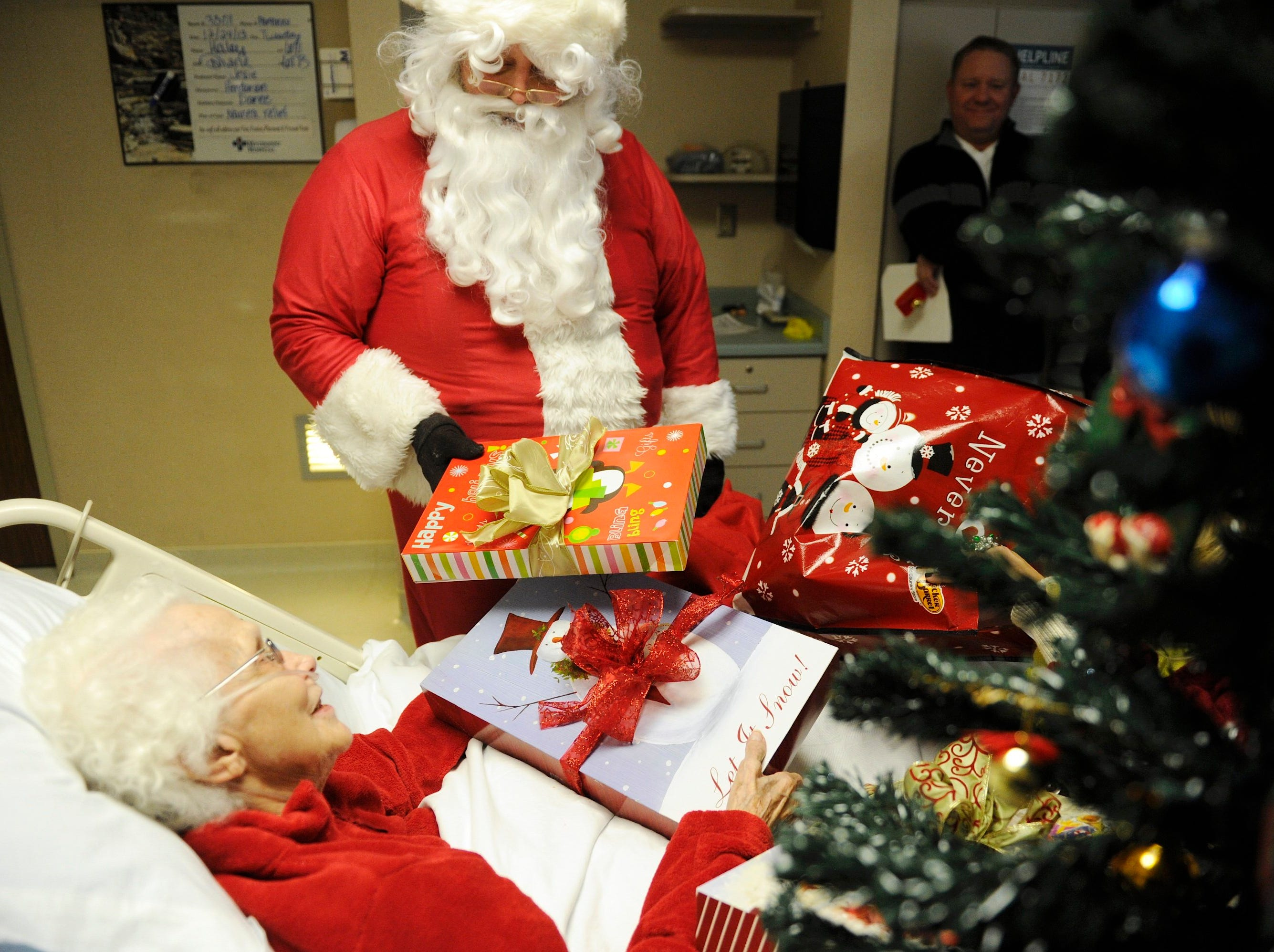 Family members and Santa, with a bag of gifts, makes a surprise Christmas Eve visit to 81 year-old Jessie Lanoux staying at Henderson's Methodist Hospital Tuesday.  12-24-2013