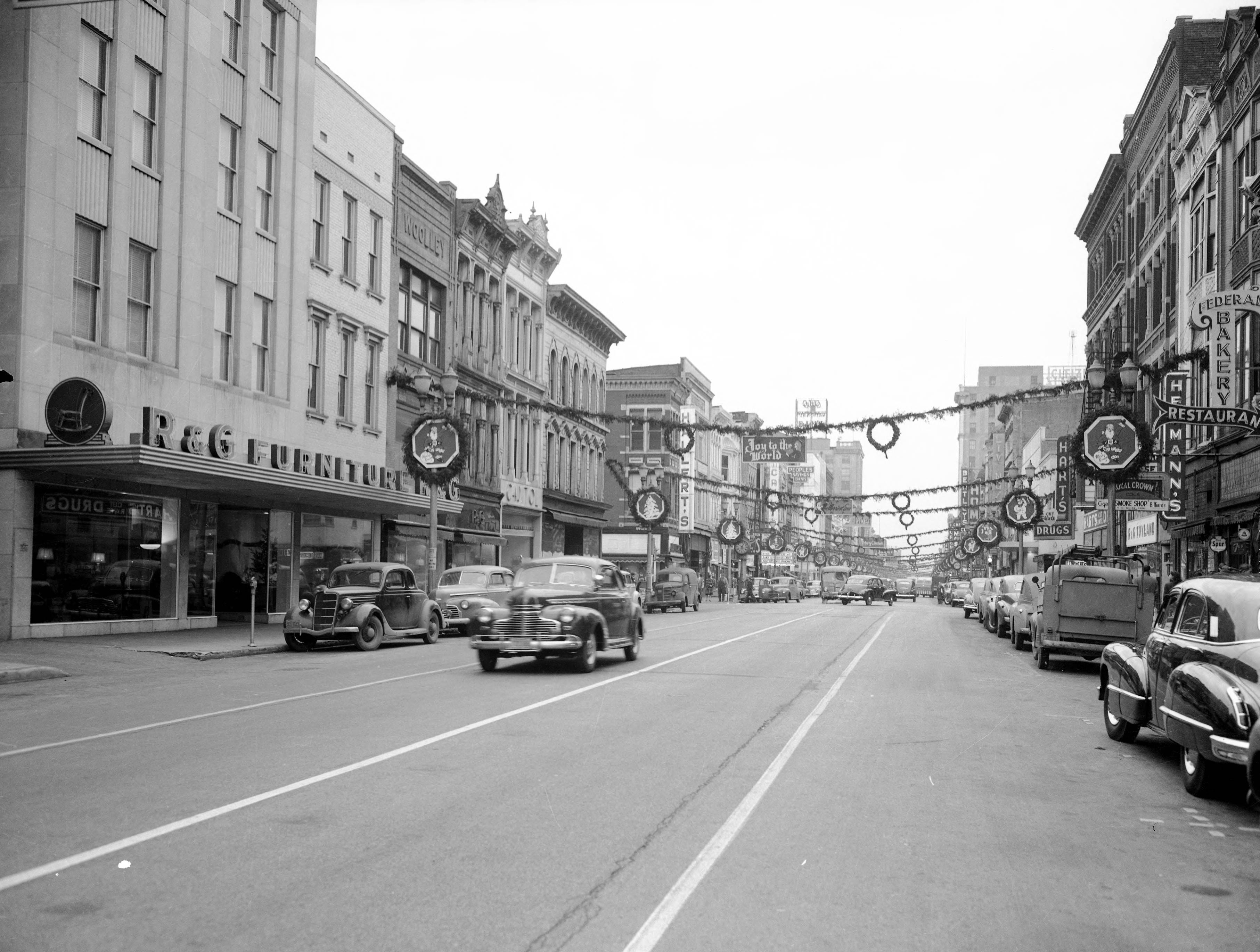 00-200 block of Main St., with Christmas decorations strung overhead, and many cars on street in 1939.