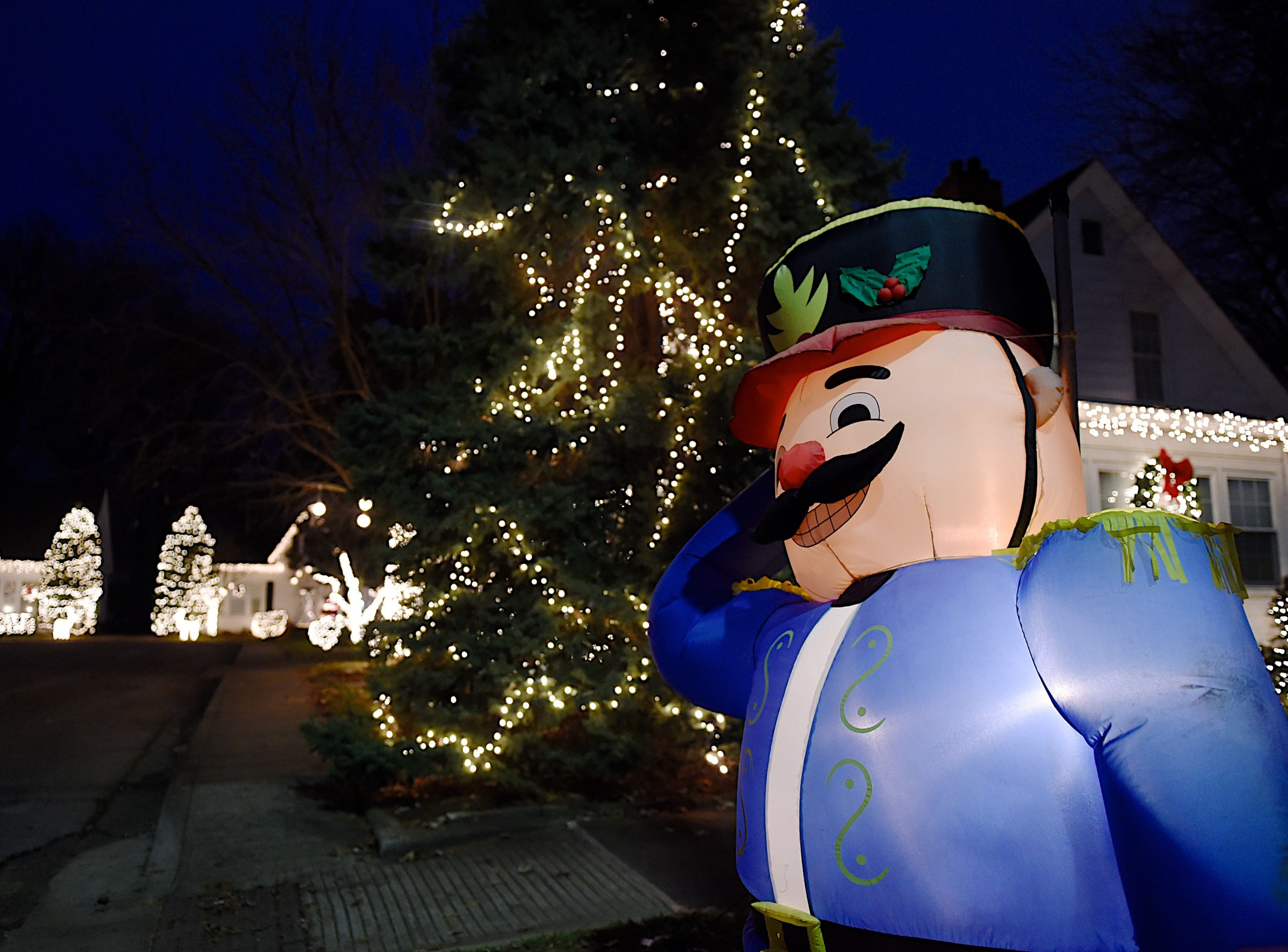One of the two guards welcomes visitors to Colonial Court's decorated homes off North Main Street Tuesday evening, December 9, 2014.