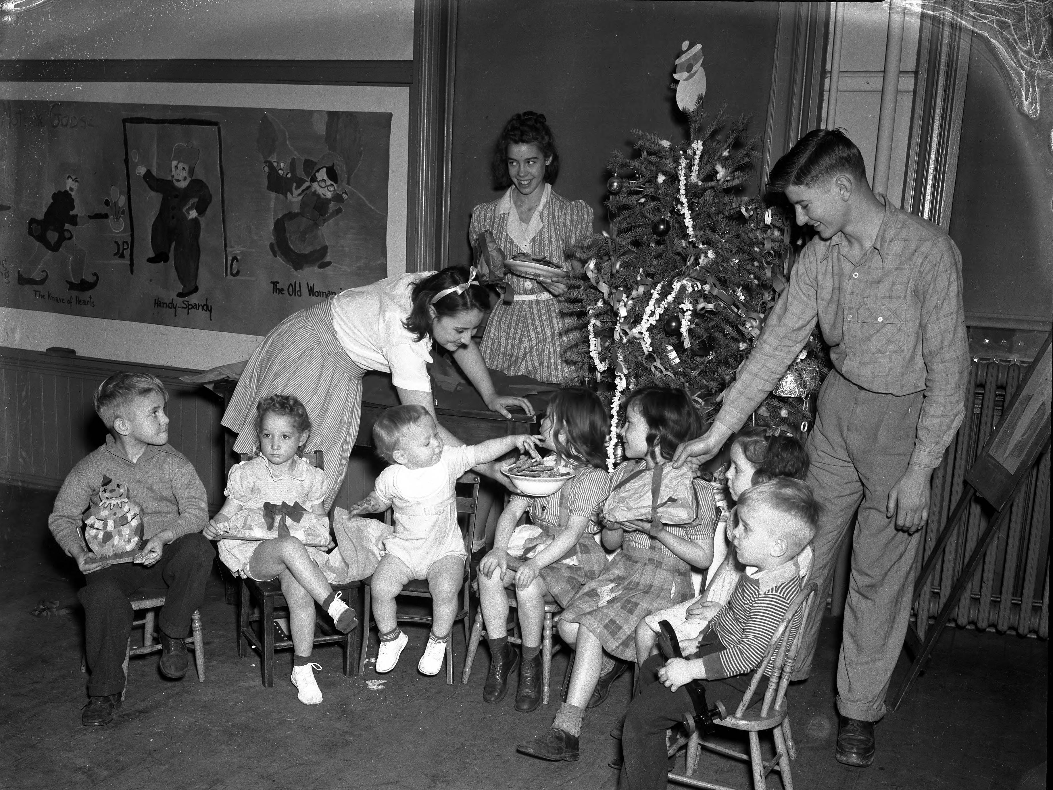 Seven little children sitting in front of a decorated Christmas tree, with older boy handing one a present and older girls holding plate and bowl of cookies.  There are primitive drawings of Mother Goose characters on the wall to the left in 1945.