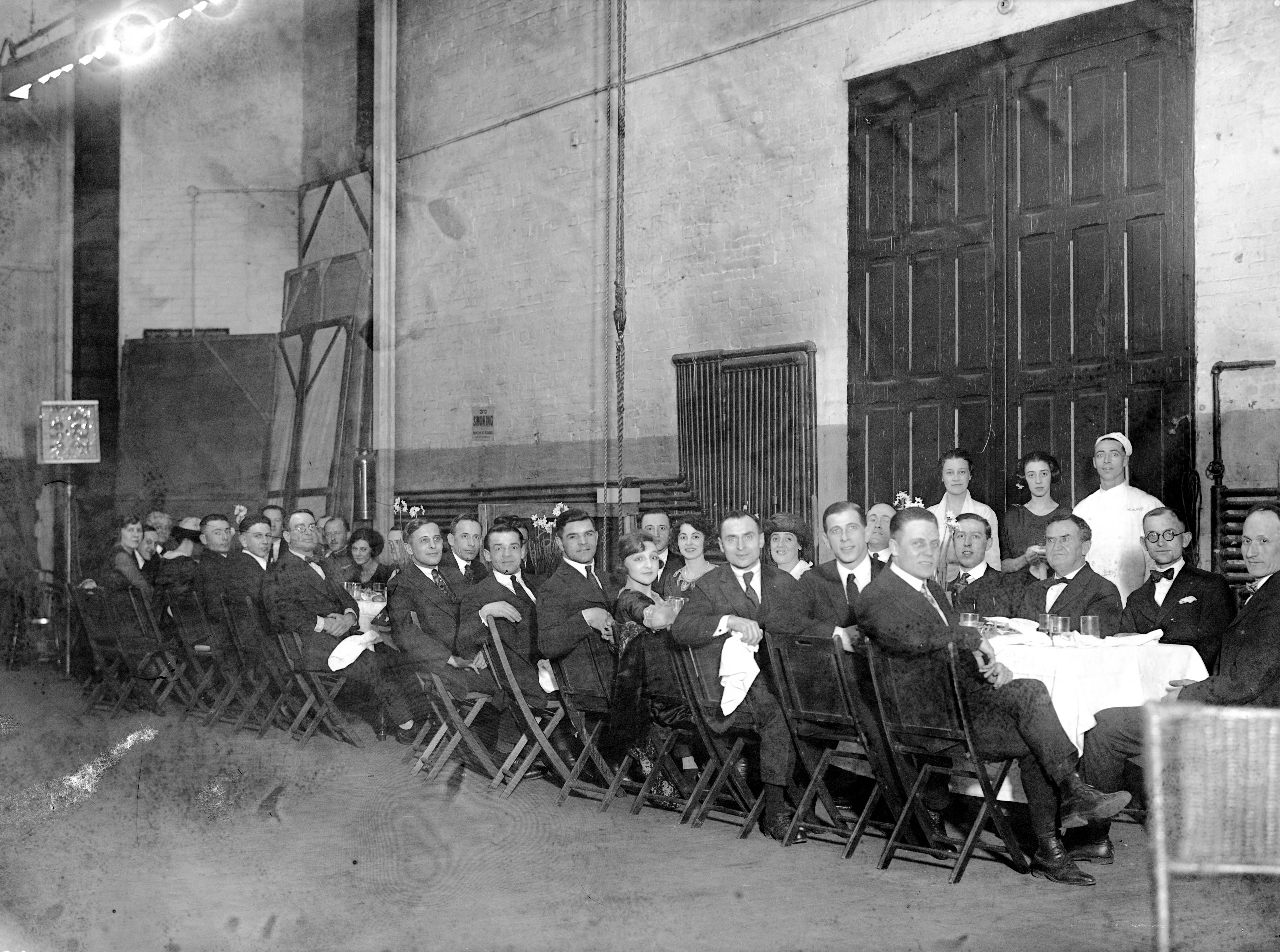 New Grand Theater (aka Grand Opera House) Christmas party for employees and vaudeville actors.  This appears to be backstage at the theatre at 209-215 Sycamore St.  Edward J. Moskowitz, the stage manager, is seated at the end of the table in 1920.