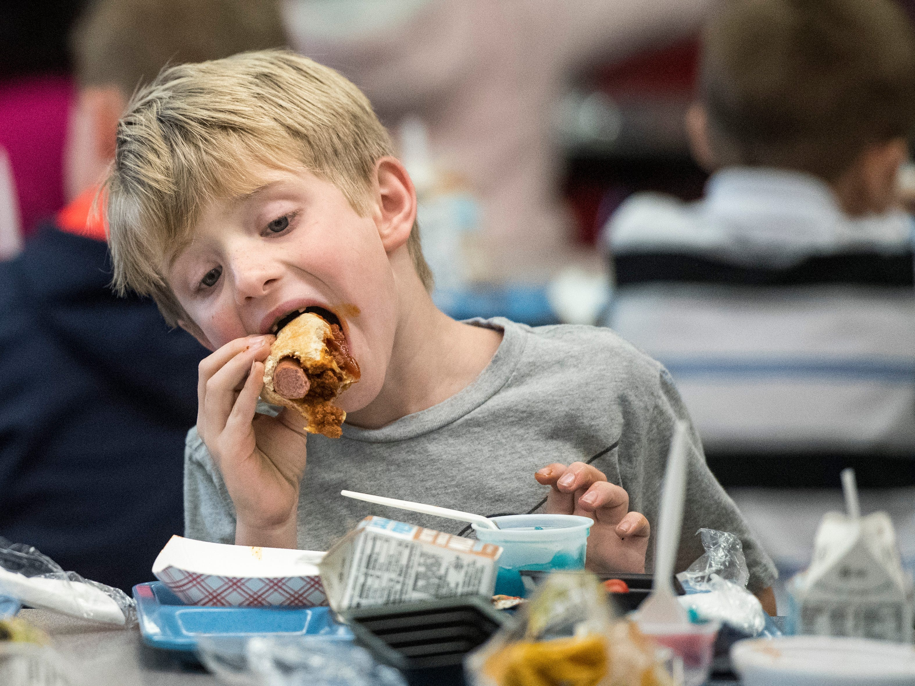 First-grader Stephen Martin chomps down on a chili dog while eating lunch at Hebron Elementary school on Friday, Oct. 19, 2018.