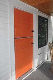Smith created a Dutch door from an old door he cut it in half to make the top and bottom doors and then painted it orange.