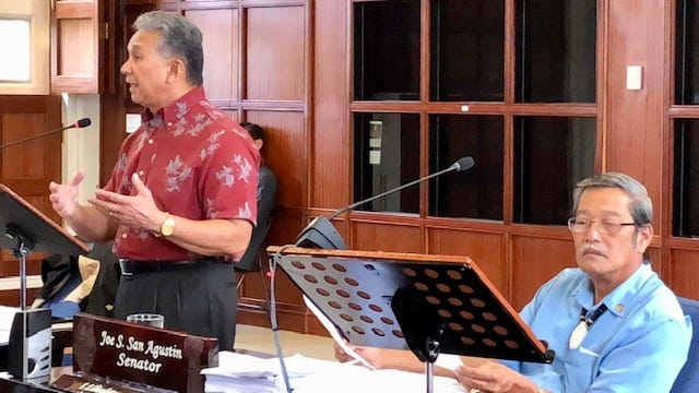 Sen. Tom Ada, left, gestures as he urges fellow senators to support an override of Gov. Eddie Calvo's veto of Bill 28, which seeks to improve the government procurement process by expanding the right to protest and setting a time limit for a decision to be made on any protest. Also in photo is Sen. Joe San Agustin, right.