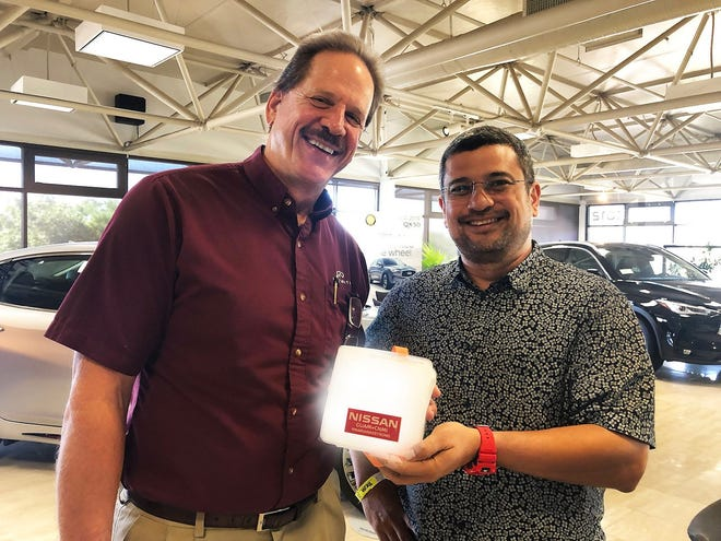 "President and CEO Van Shelly of Nissan Guam presents Ryan ""Boss"" Alvarez of Joeten Motor Company with a portable solar-powered lantern and cell phone charger system.  Nissan Guam donated 500 of these lanterns to assist the families in the CNMI affected by Super Typhoon Yutu."