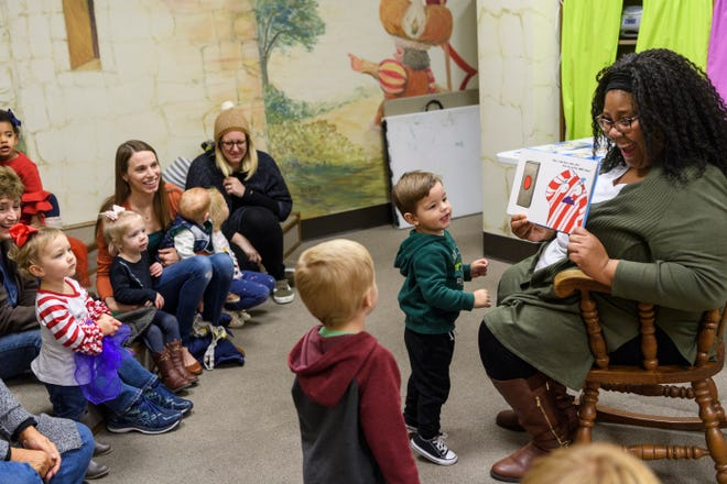 "Children's Services Manager Danielle Anguish, right, reads ""Don't Push the Button! A Christmas Adventure,"" an interactive children's book by Bill Cotter, during the last Toddler Tales program of the year at Henderson County Public Library, Wednesday morning, Nov. 28, 2018."