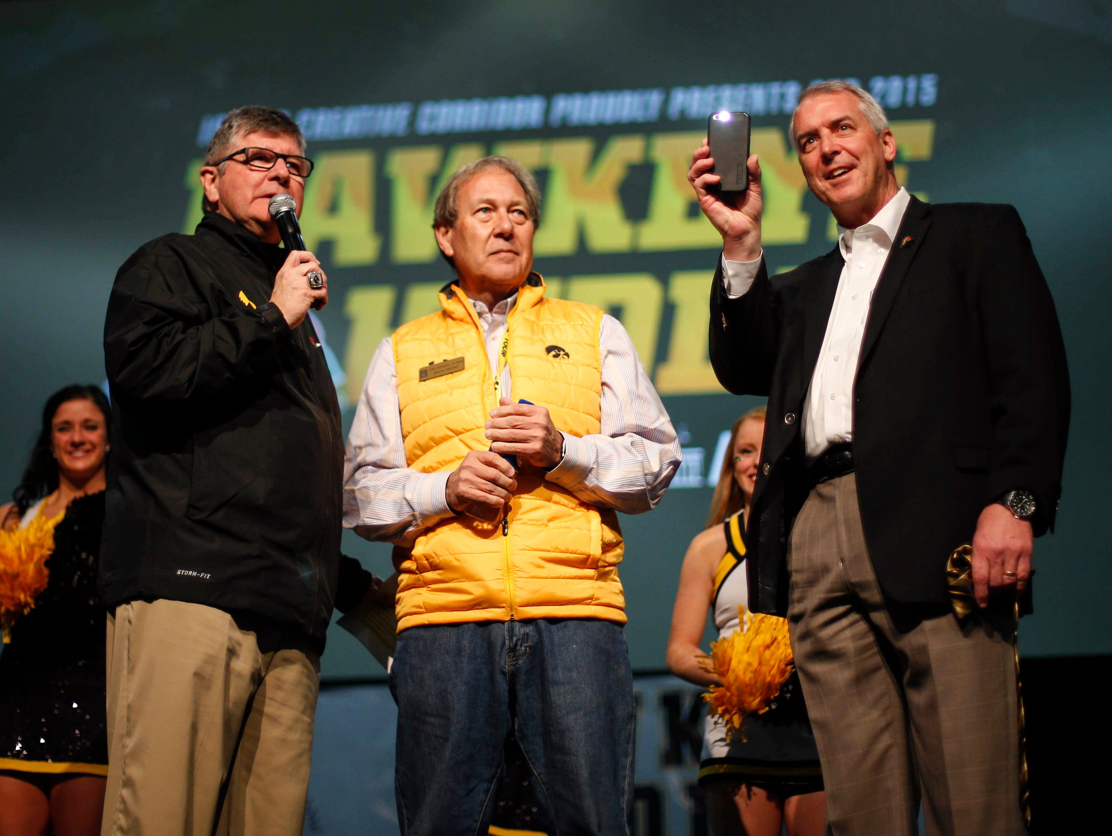 University of Iowa Athletic Director Gary Barta holds his cell phone with the flashlight lit, illustrating the new trend at the start of the fourth quarter during Iowa Hawkeye football games. Barta, joined by president Bruce Herreld, center, and Gary Dolphin, spoke during the Hawkeye Huddle at the Los Angeles Convention Center on Wednesday, Dec. 30, 2015, in Los Angeles, Calif.