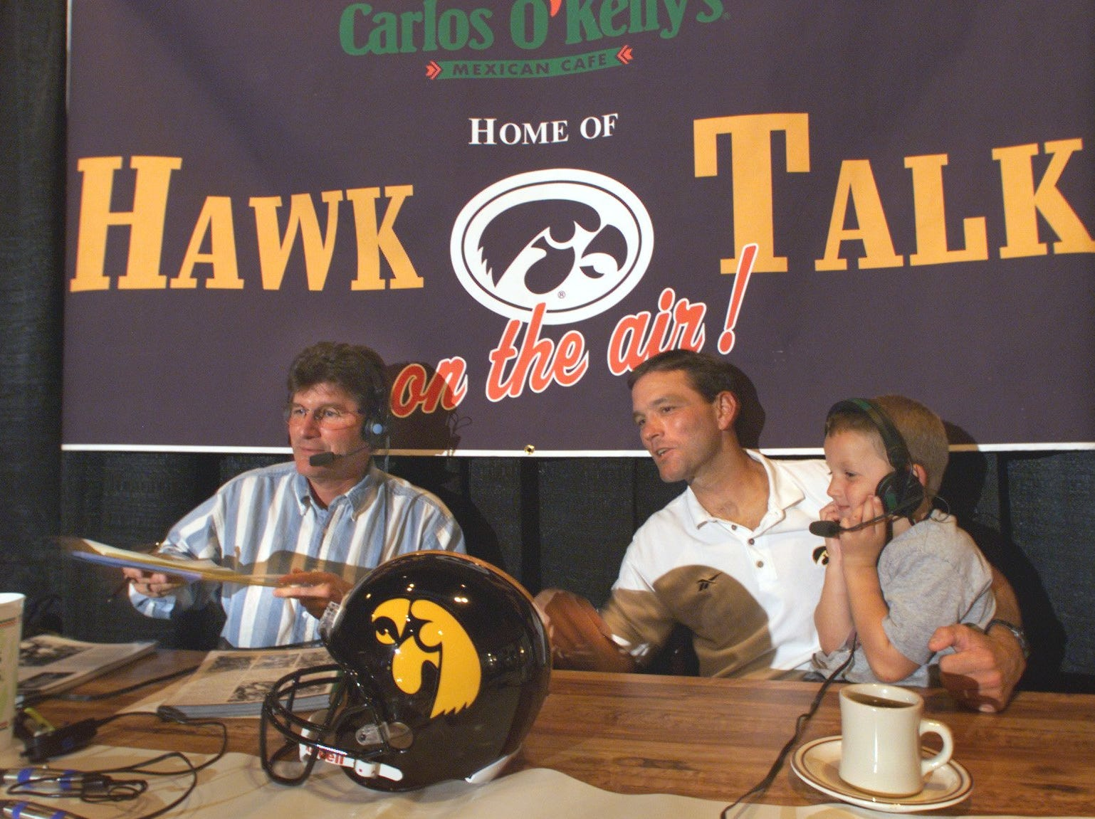 From 1999: Iowa football coach Kirk Ferentz holds his son, Steve, on his lap during the coach's weekly call-in show at Carlos O'Kelly's in Iowa City. At left is Iowa radio broadcaster Gary Dolphin.