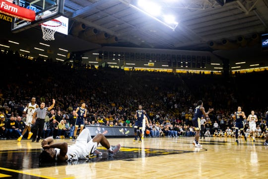 Iowa forward Tyler Cook (left) holds his head after taking a fall during a NCAA men's basketball game on Tuesday, Nov. 27, 2018, at Carver-Hawkeye Arena in Iowa City.