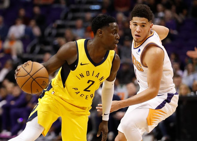 Indiana Pacers guard Darren Collison (2) drives as Phoenix Suns guard Devin Booker defends during the first half of an NBA basketball game, Tuesday, Nov. 27, 2018, in Phoenix.