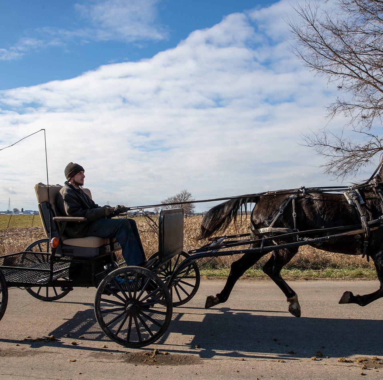 An Amish man rides down a road near Shipshewana, Ind., on Tuesday, Nov. 20, 2018.