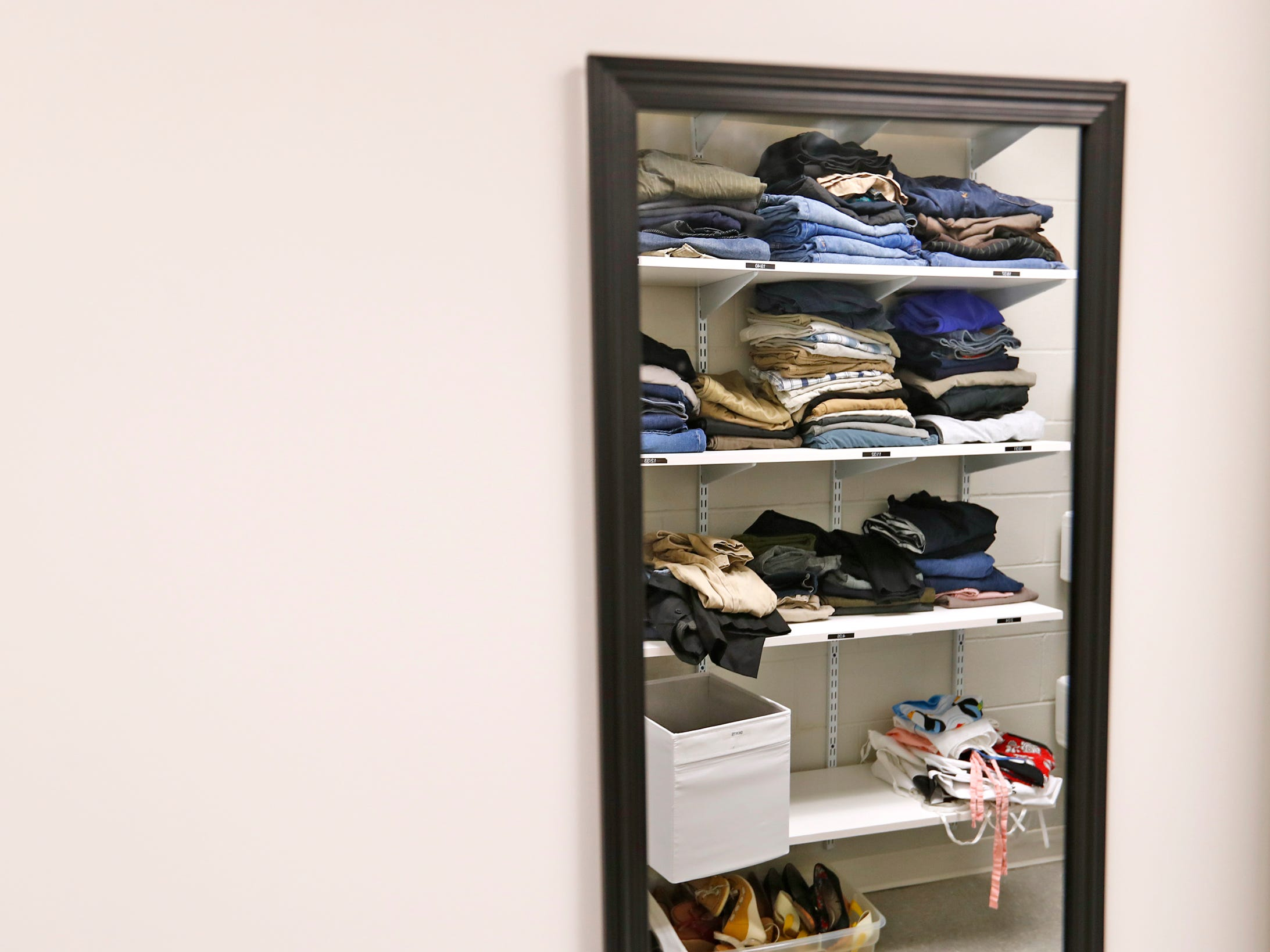 Shelves with clothes for youth are seen reflected in a mirror at Indiana Youth Group, Tuesday, Nov. 27, 2018.  The organization offers a safe drop-in center for LGBTQ+ youth, ages 12-20, and their straight ally friends, in the Indianapolis area.  Activities, tutoring, food and clothes pantries are included in the center.