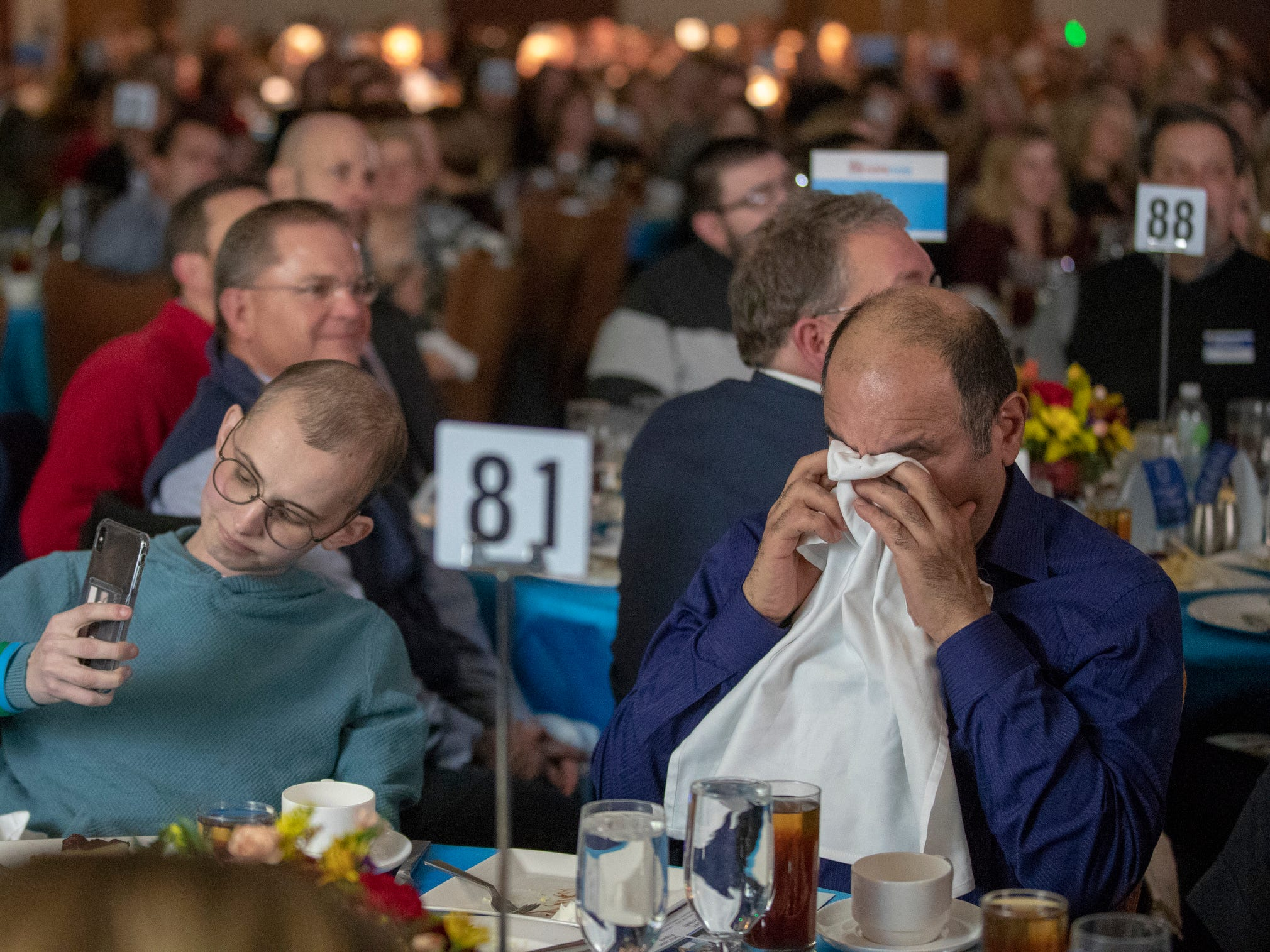 Tyler Trent records a video of him talking as cancer researcher Reza Saadatzadeh, PhD, wipes away tears at a fundraiser luncheon for Riley Children's Foundation's Be The Hope Now campaign, Indianapolis, Wednesday, Nov. 28, 2018. Trent, who has the rare bone cancer osteosarcoma, is in hospice care, and was given the Sagamore of the Wabash award, given to distinguished Hoosiers.