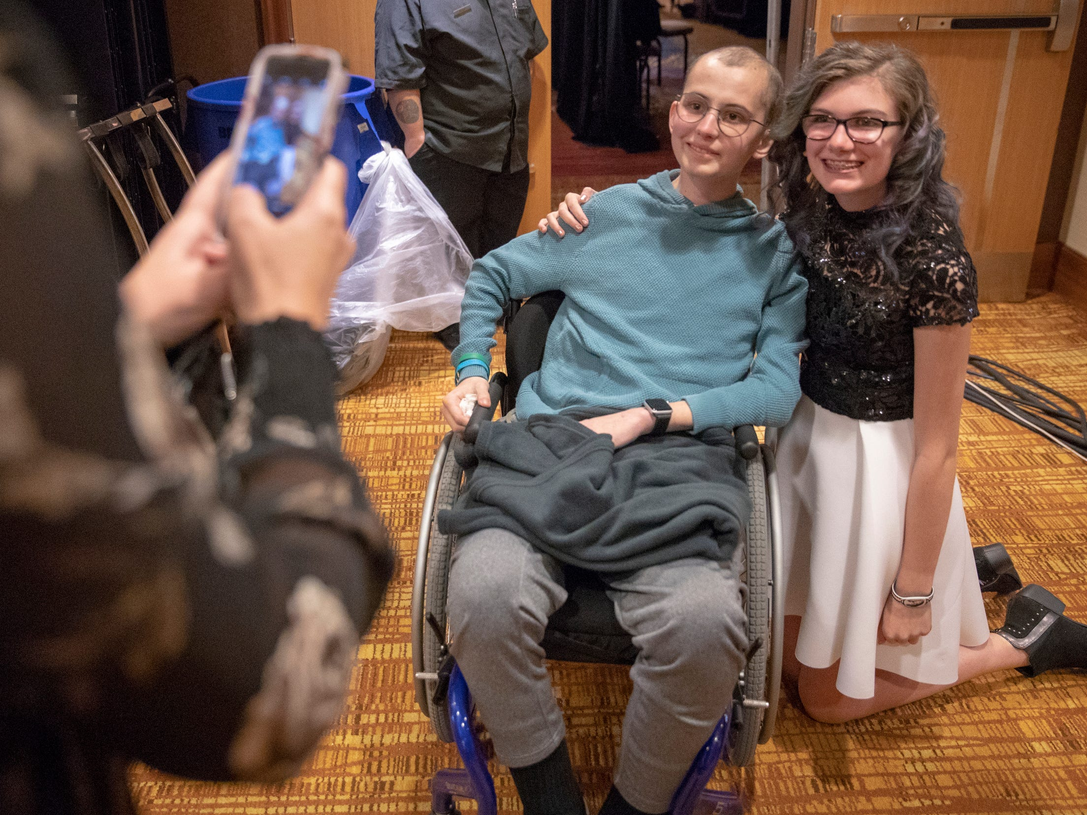 Olivia Pierce, 12, Hobart, who is dealing with the effects of bilateral retinoblastoma, poses with Tyler Trent as her mother Shannon Pierce snaps a photo at a fundraiser luncheon for Riley Children's Foundation's Be The Hope Now campaign, Indianapolis, Wednesday, Nov. 28, 2018. Trent, who has the rare bone cancer osteosarcoma, is in hospice care, and was given the Sagamore of the Wabash award, given to distinguished Hoosiers.
