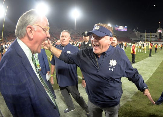 Notre Dame Fighting Irish coach Brian Kelly celebrates with athletic director Jack Swarbrick after the game against the Southern California Trojans at Los Angeles Memorial Coliseum. Notre Dame defeated USC 24-17.