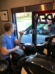 Cafezinho Coffee Company recently opened a drive-through window at its headquarters at 1201 Clinton Industrial Park Drive in Clinton. Paul Farrar, left, of Clinton, operations manager at Cafezinho Coffee Company, speaks with Dr. David Parks, a customer.