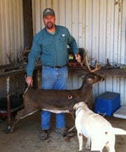 Scott Cannada is 6-feet, 1-inch tall and dwarfs the mature buck recently harvested by his wife.